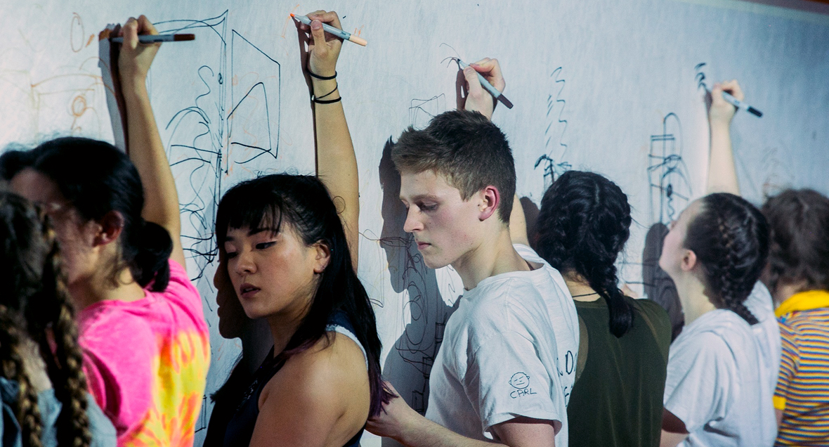 Young dancers write on a white wall above their heads with marker pens. Youth Dance Company, Melbourne. Yellow Wheel
