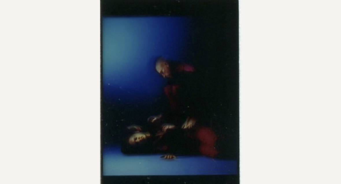 A blurred image of a dancer lying on a blue floor and another dancer crouching behind them