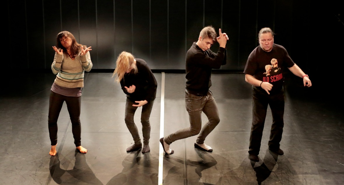 Four performers stand in different positions.