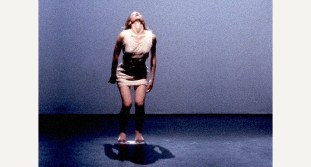 A dancer in a short white dress arches their back to look up while leaning forward in a blue room