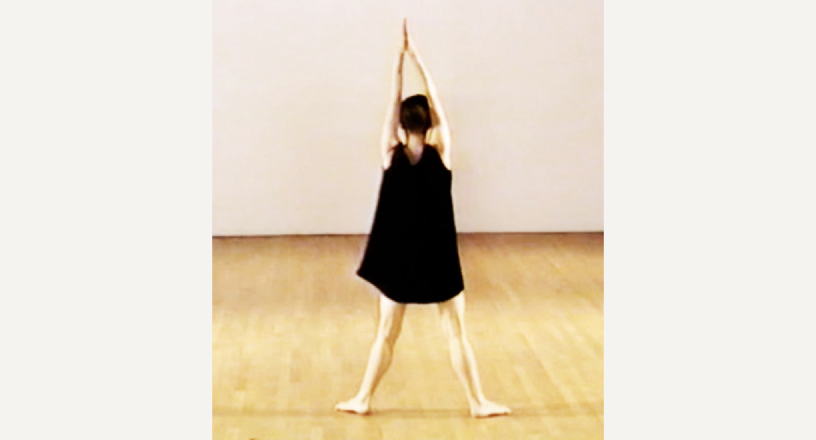 A dancer in a short black dress faces away with feet apart and arms held aloft, palms together in a large room with light wood floors and white floor