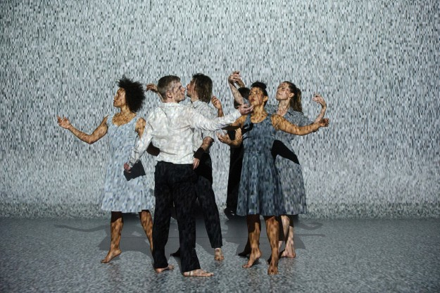 Dancers stand in a tight group with their arms held aloft, in front of a projection of static.