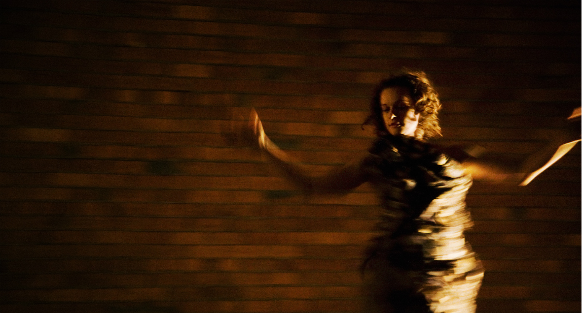 Dancer Carlee Mellow frontlit in a gold dress spinning in front of a brick wall