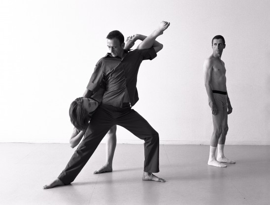 A dancer lunges to their side to support another who leans forward with one leg extended up. A third dancers looks on in their underwear in the background
