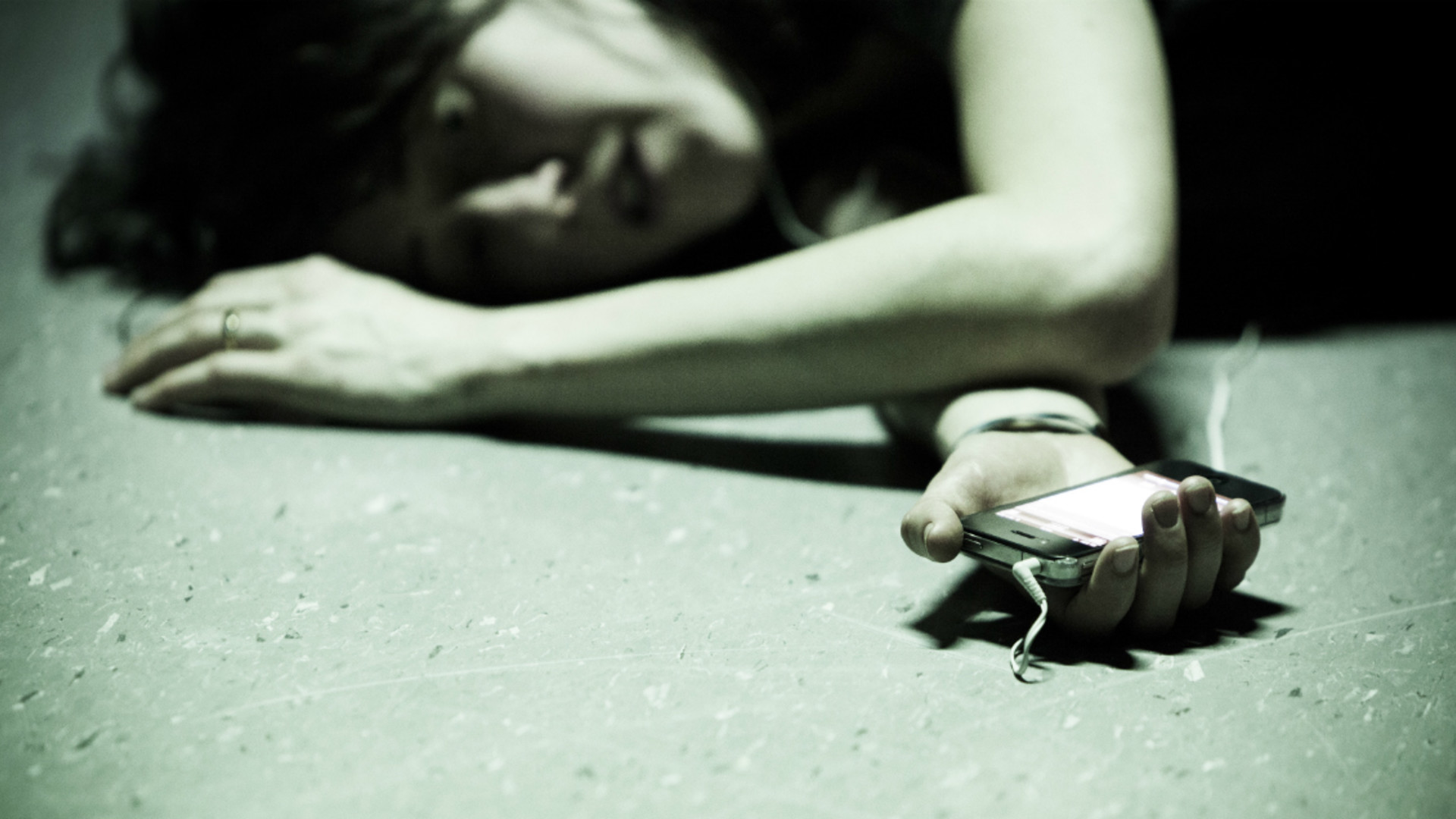 A performer lies on the ground, with her arm outstretched holding her iPhone.