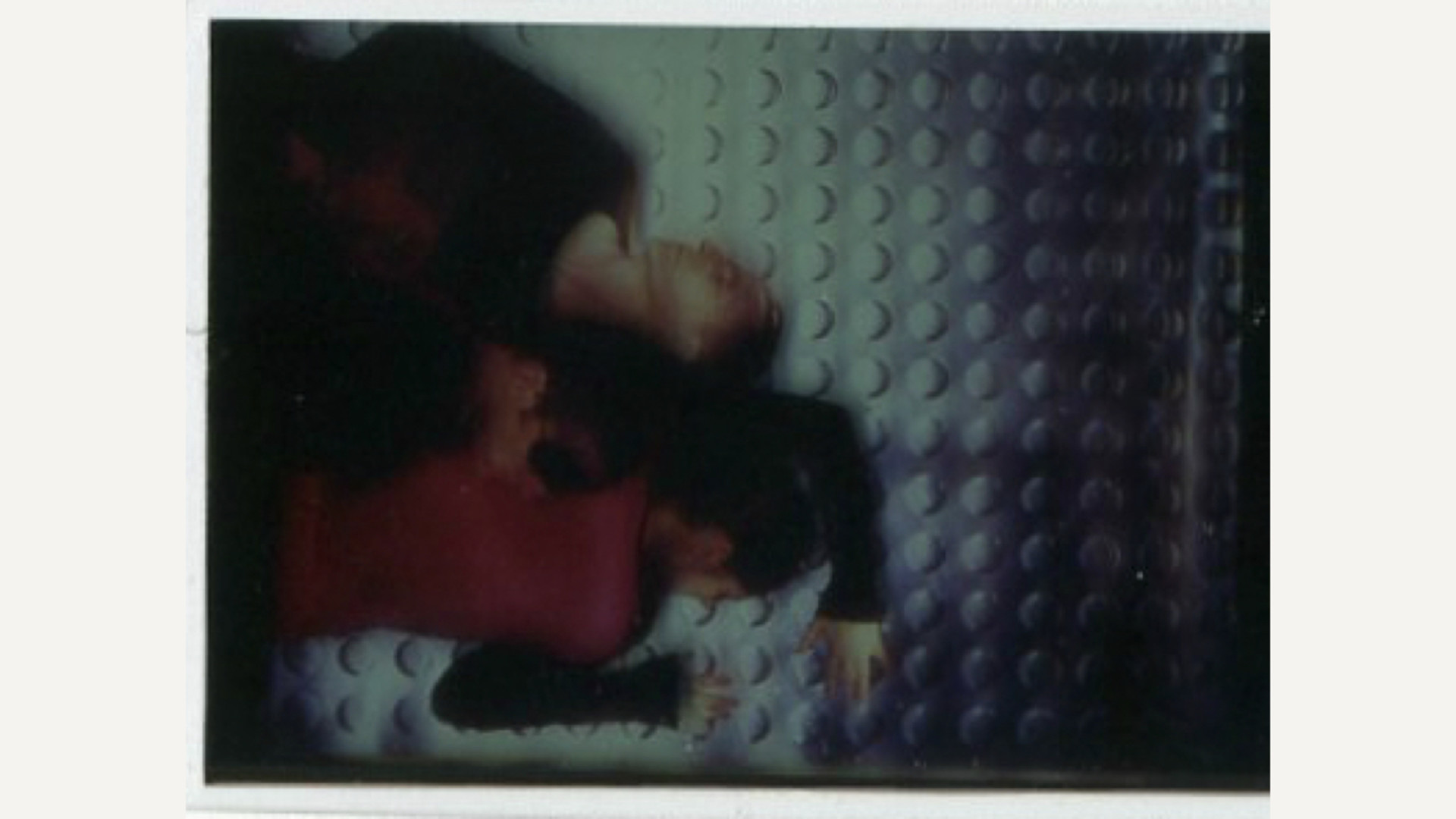 A blurred image of two dancers lying next to each other on a metallic surface dotted with small holes