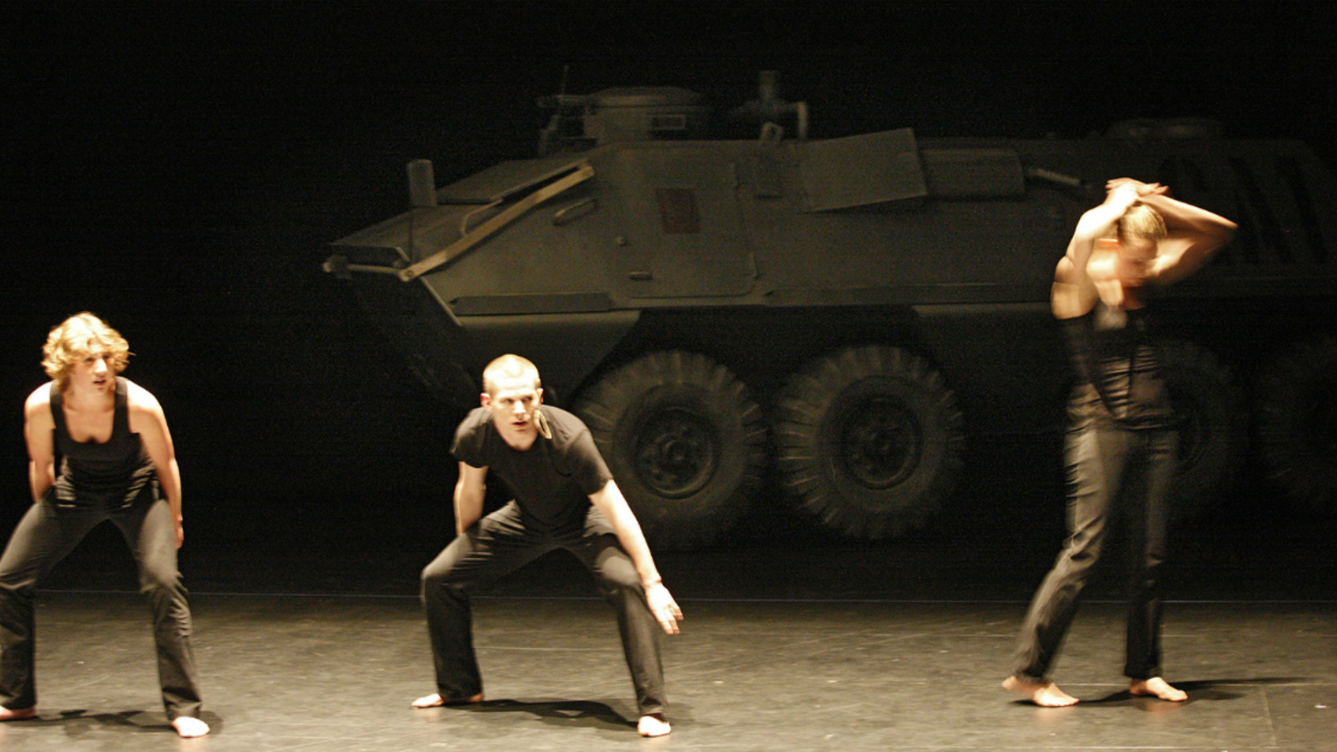 Two dancers crouch with their hands on the knees while another stands to the side with their hands on their head.