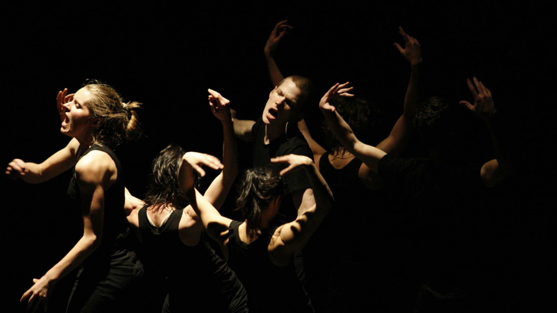 Dancers stand in a close group, facing different directions, with their mouths open wide.