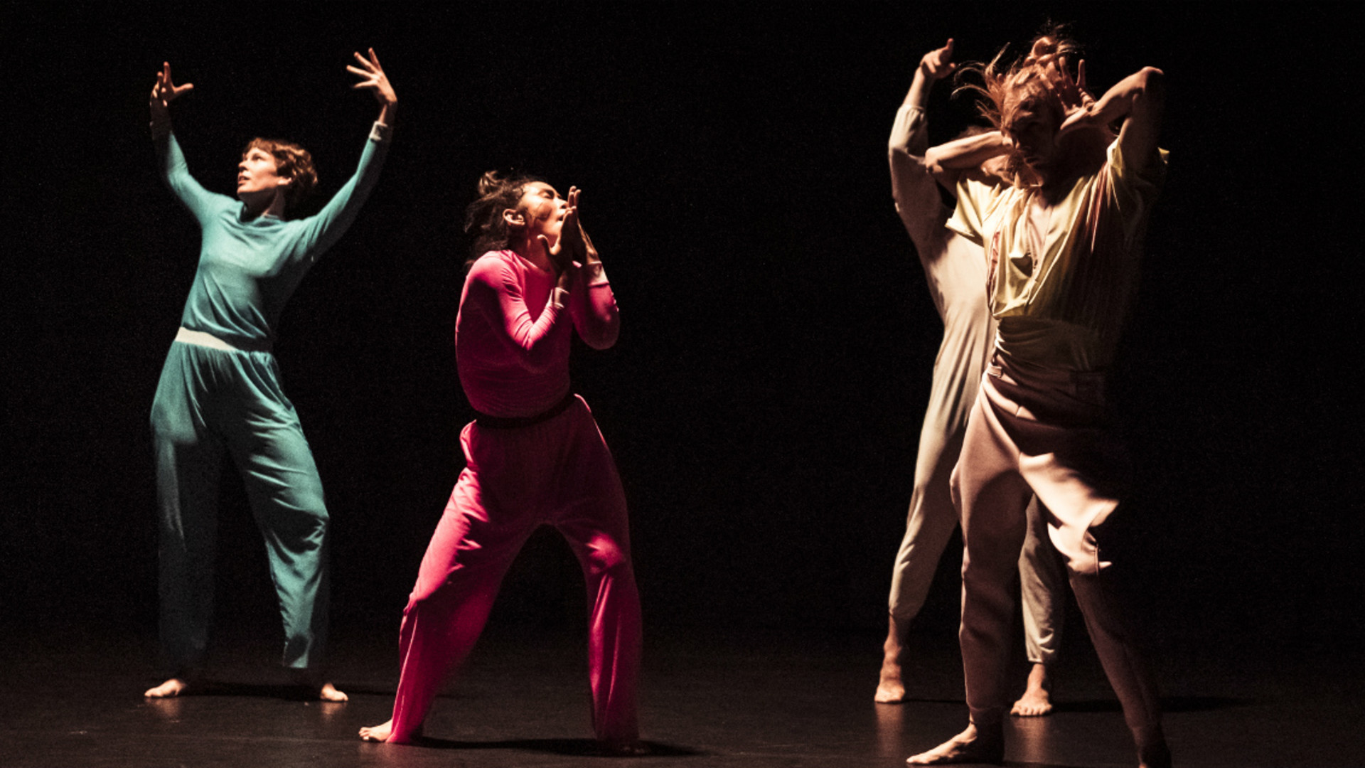 One dancer holds her arms above her head, another holds her hands over her mouth while two more stand to the side with their hands in the air.