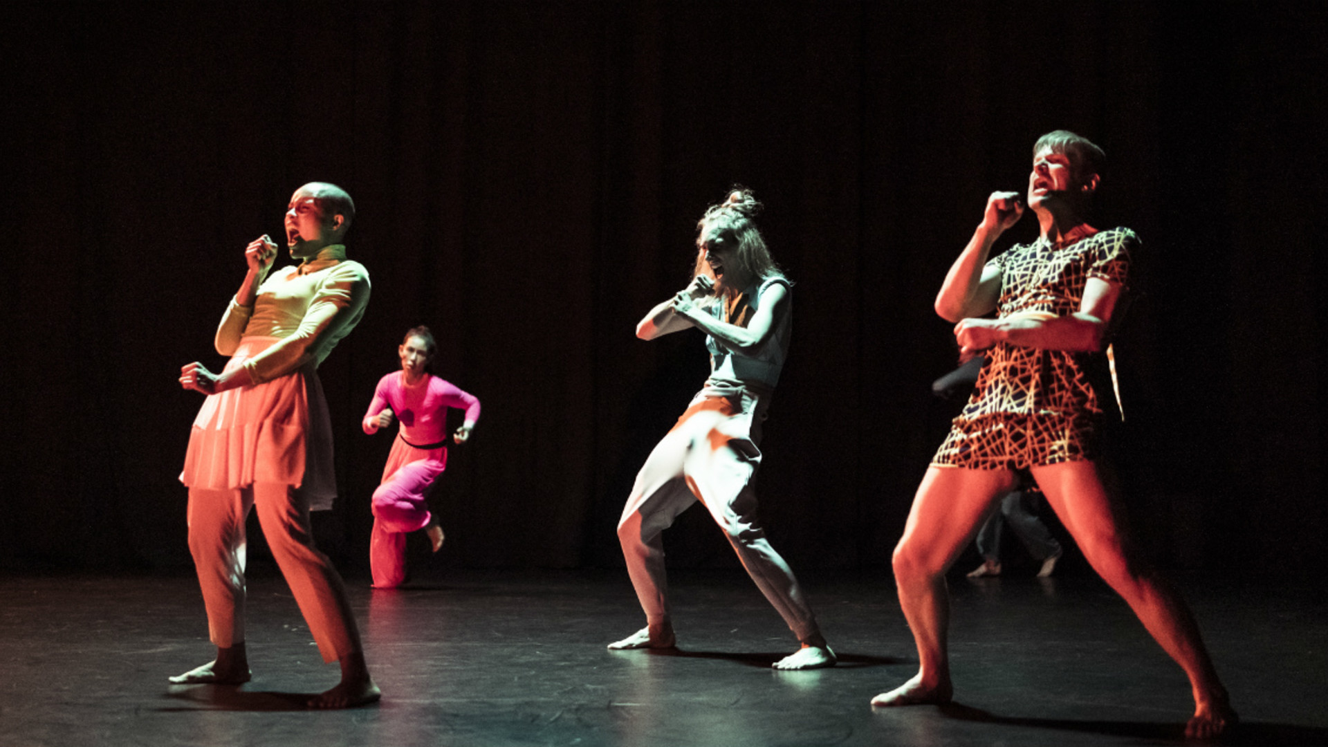 Three dancers hold their arms up, miming singing into microphones while a dancer in the background runs towards them.
