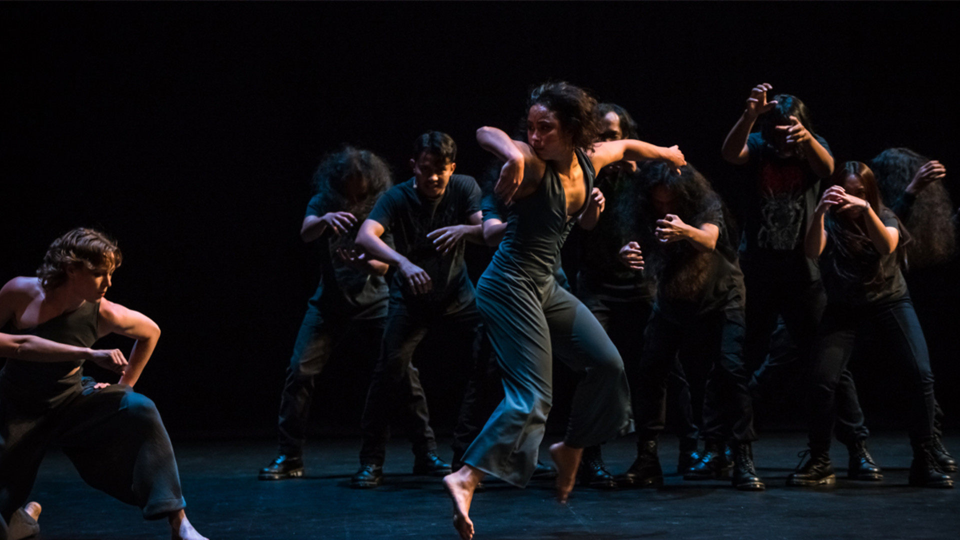 One dancer leaps, arms lifted while another crouches low to the side, as singers hover in the background.