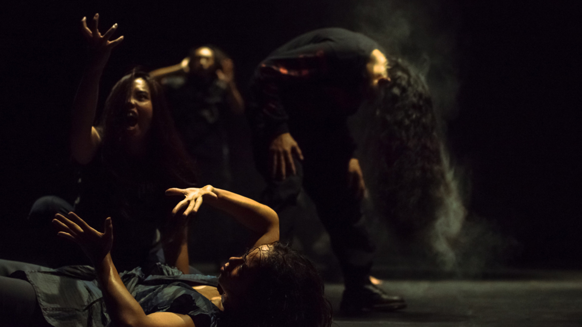 A dancer lies on the ground, arms lifted while one singer hovers over her. Another singer is bent over in the background, with his head down. Smoke billows from his long hair.