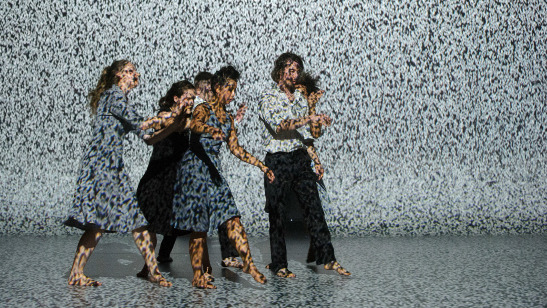 A group of dancers move in a tight group in front of a projection of static.
