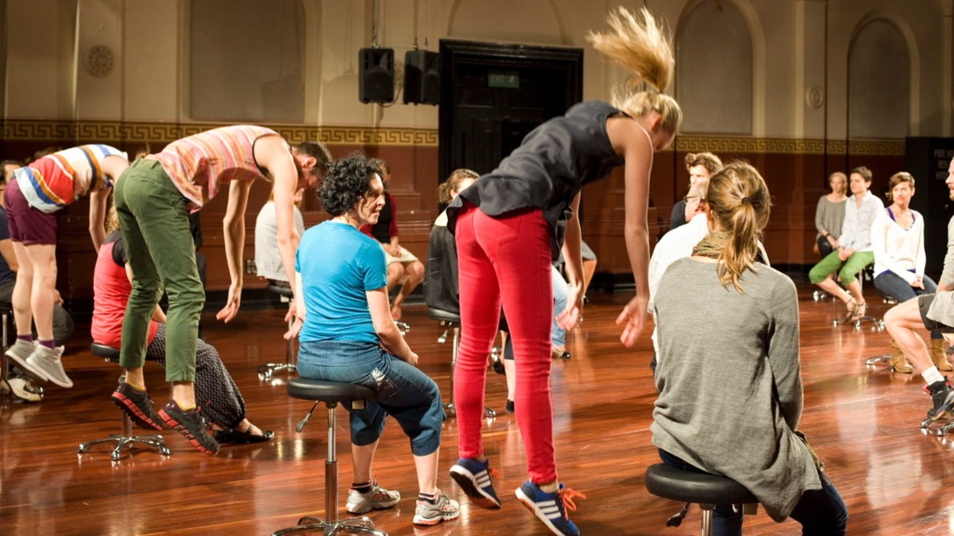 Dancers dressed in bright everyday clothes jump leaning forwards with arms hanging down interspersed with people watching them sitting on round stools in a large bright hall with shiny wooden floor