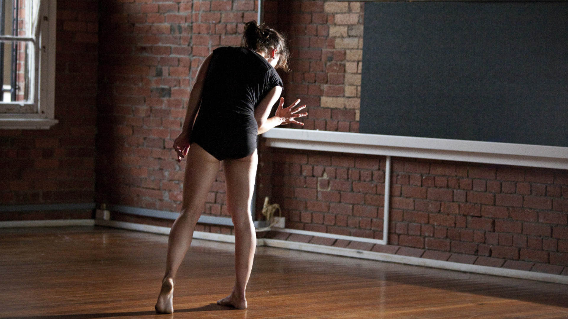 A woman, Deanne Butterworth, in a black leotard leans to her right with her arm bent at the elbow facing a blackboard on a brick wall