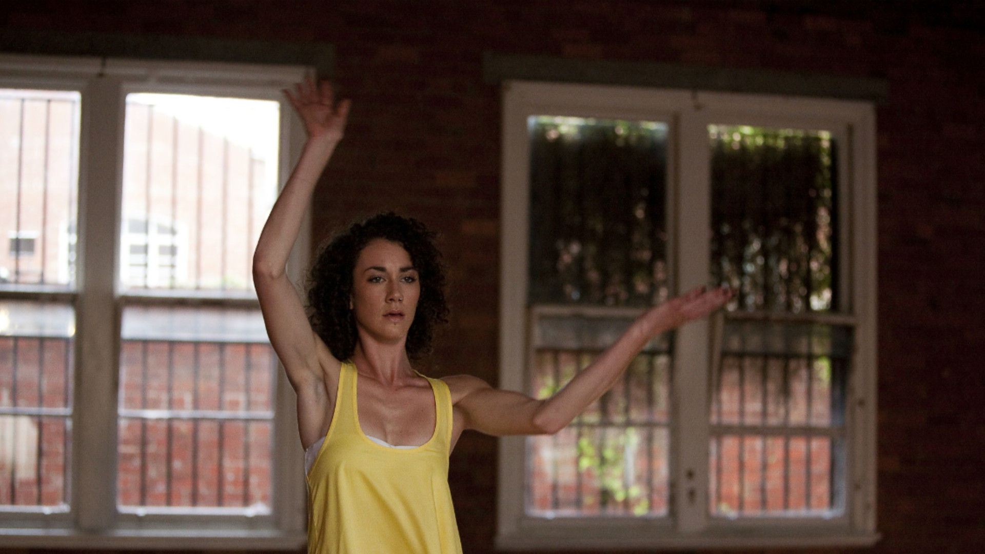 A woman in a yellow top, Frankie Snowden, holds her arms up and looks intently forwards with two windows behind her.