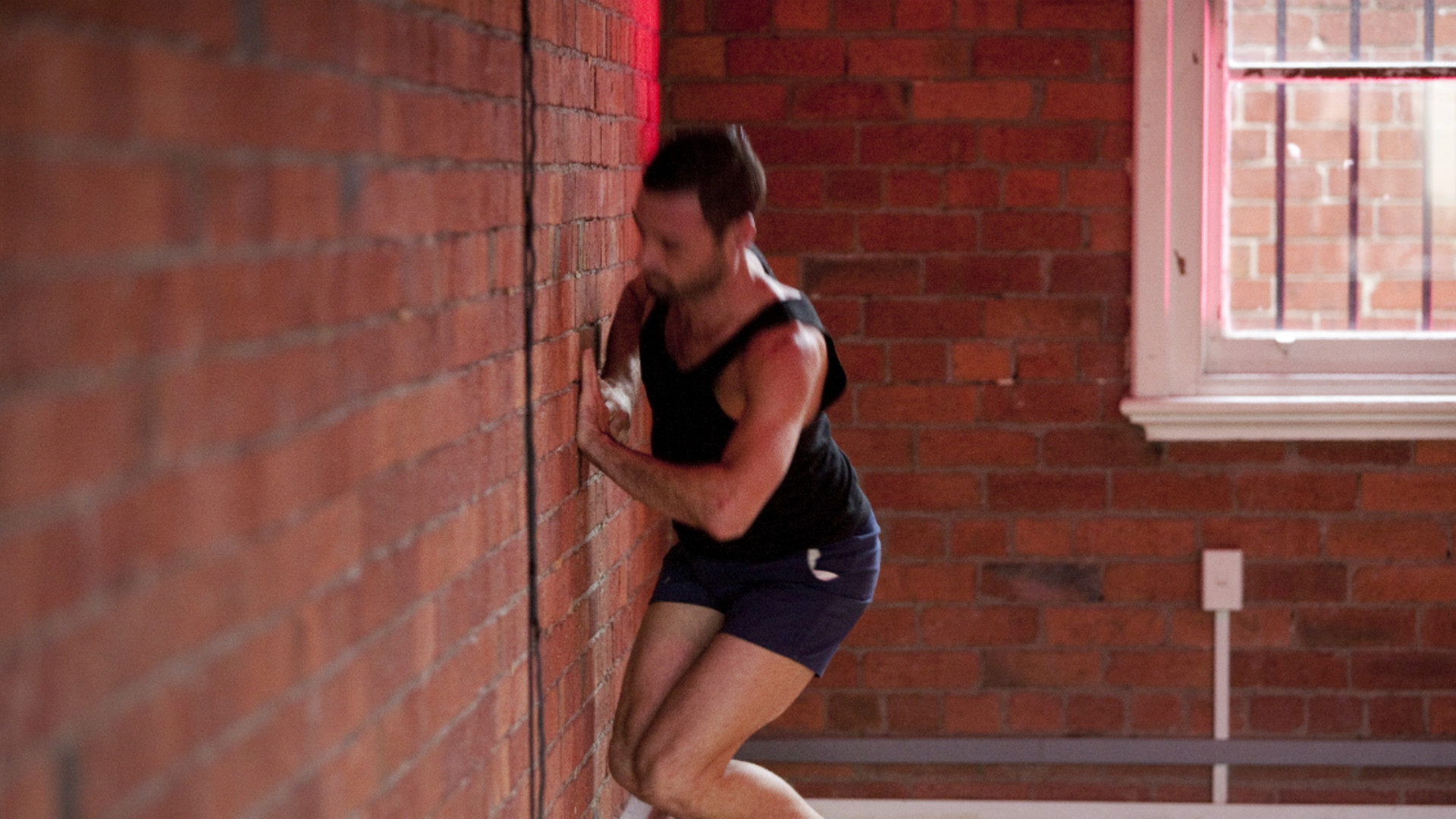 A man, Matthew Day, squats in front of a brick wall and is blurred by the dynamic action