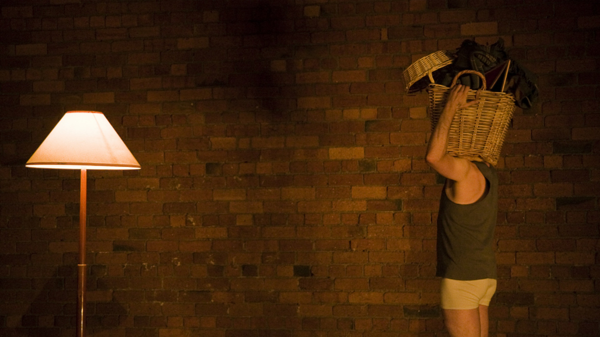 A male dancer holding a basket on his shoulder and facing a lit standard lamp in front of a brick wall