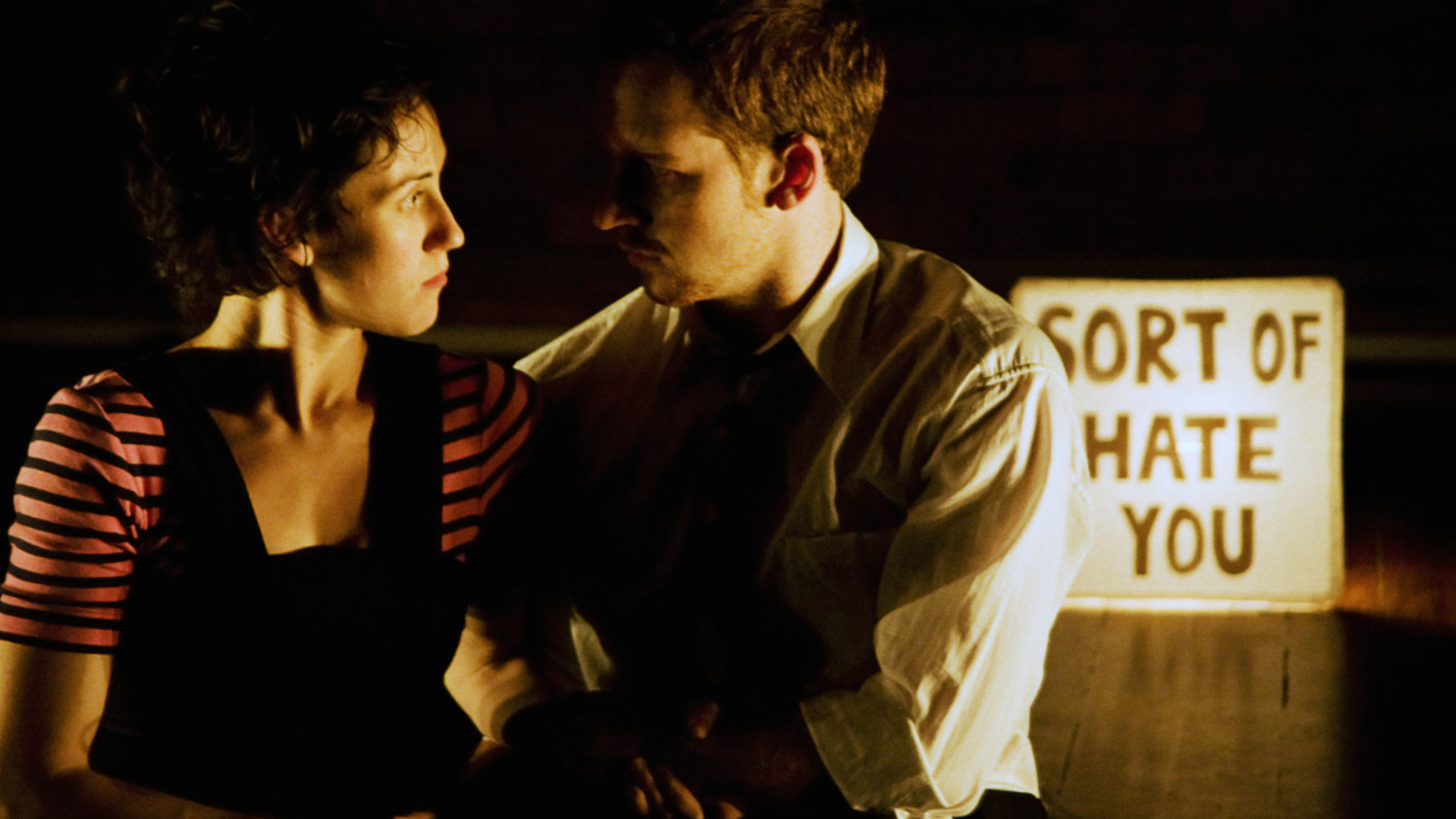 A man in a white shirt and a woman in black and pink stripes embrace solemnly in front of a lit sign that reads Sort of Hate You