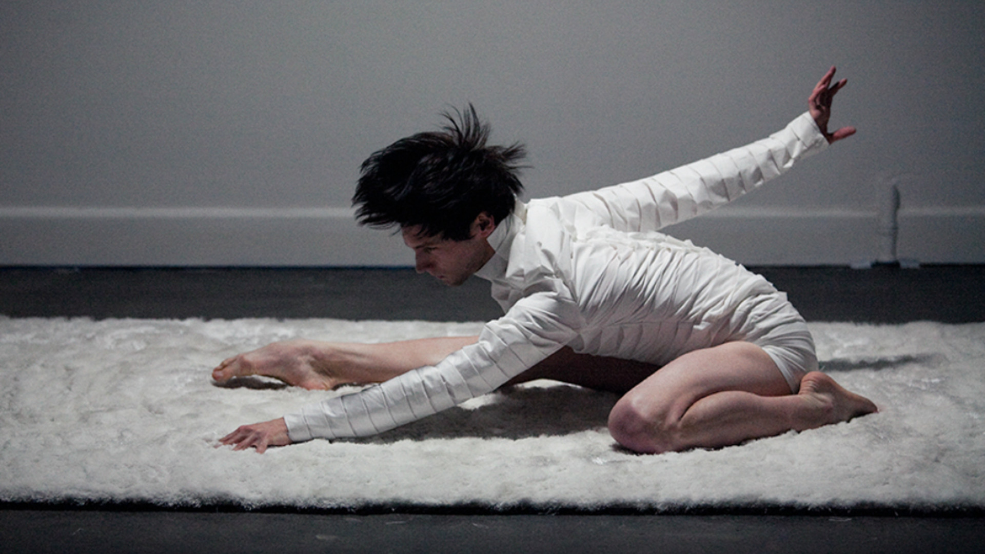 A male dancer dressed in white drops down onto a white rug dynamically with an intense focus forward