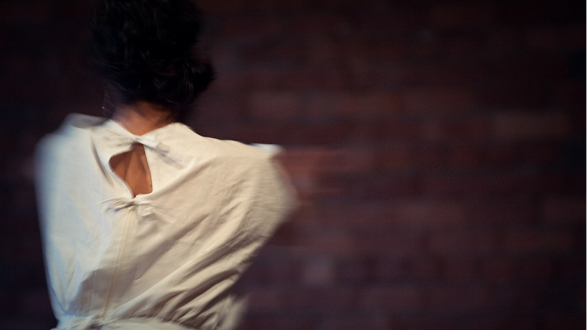 A blurred image of the back of the torso of a  woman dressed in white, perhaps caught mid-spin