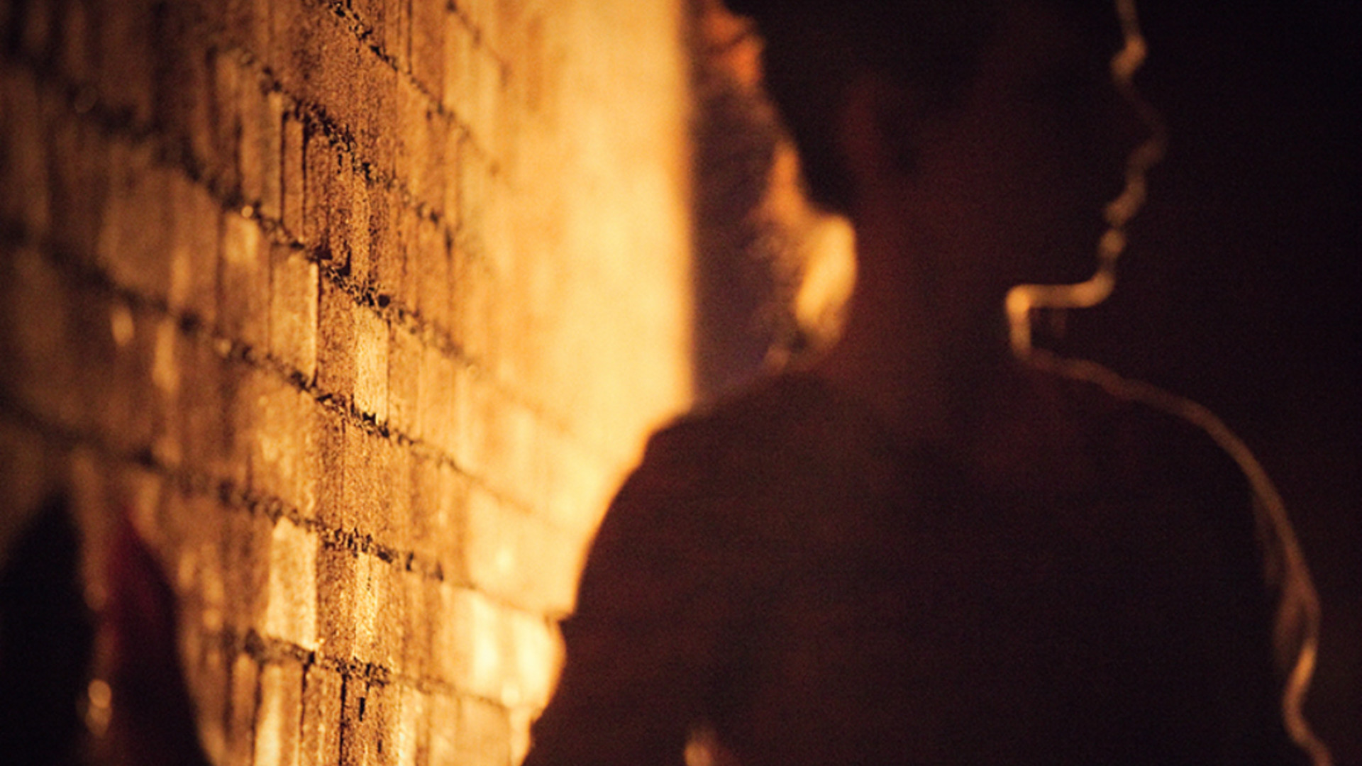 A blurred close-up of a woman facing right and touching a brick wall on the left. The bricks, lit yellow, are in focus