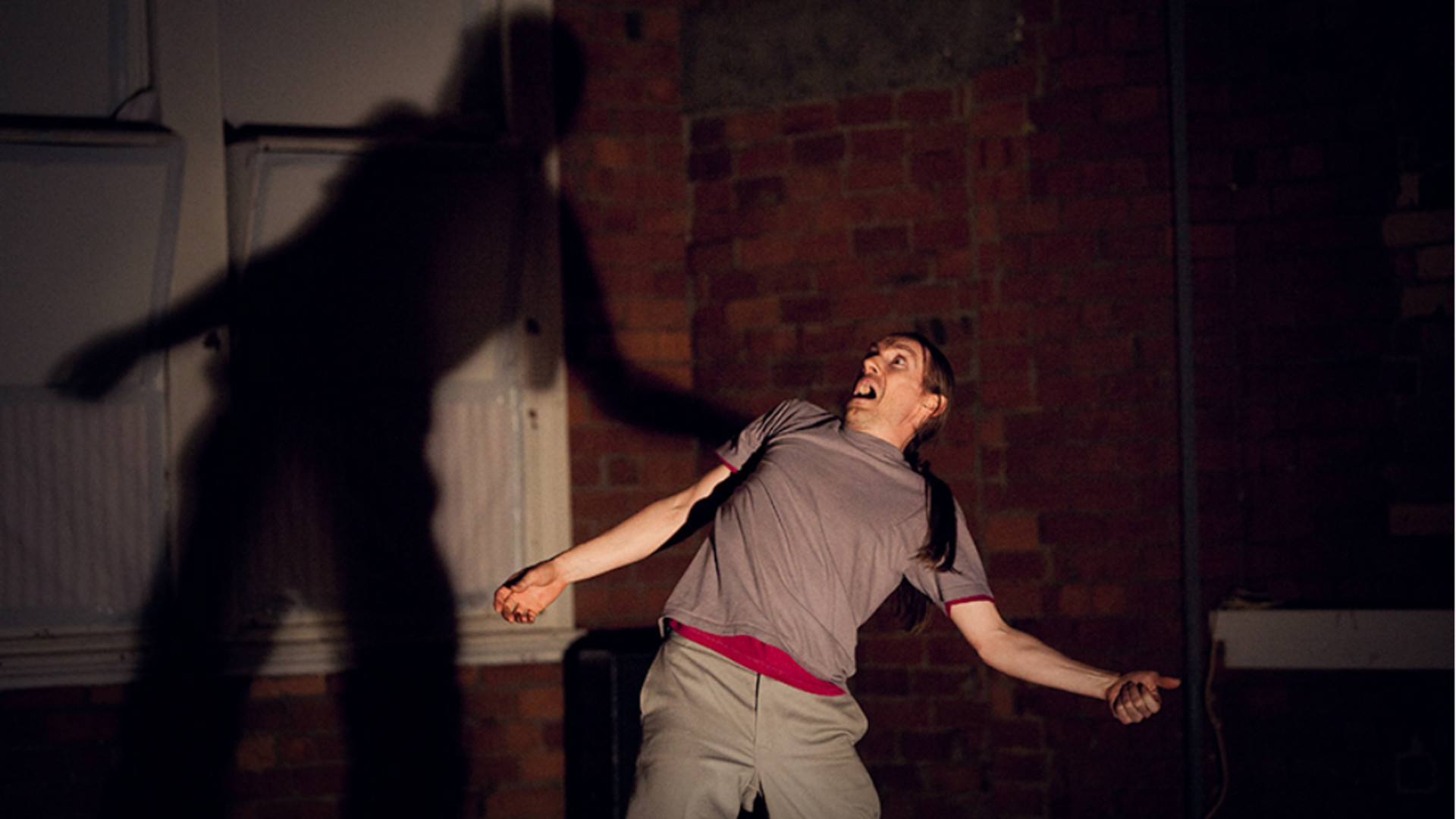 A male dancer with long hair and leans backward with a shocked expression, his shadow large on the brick wall and window behind him