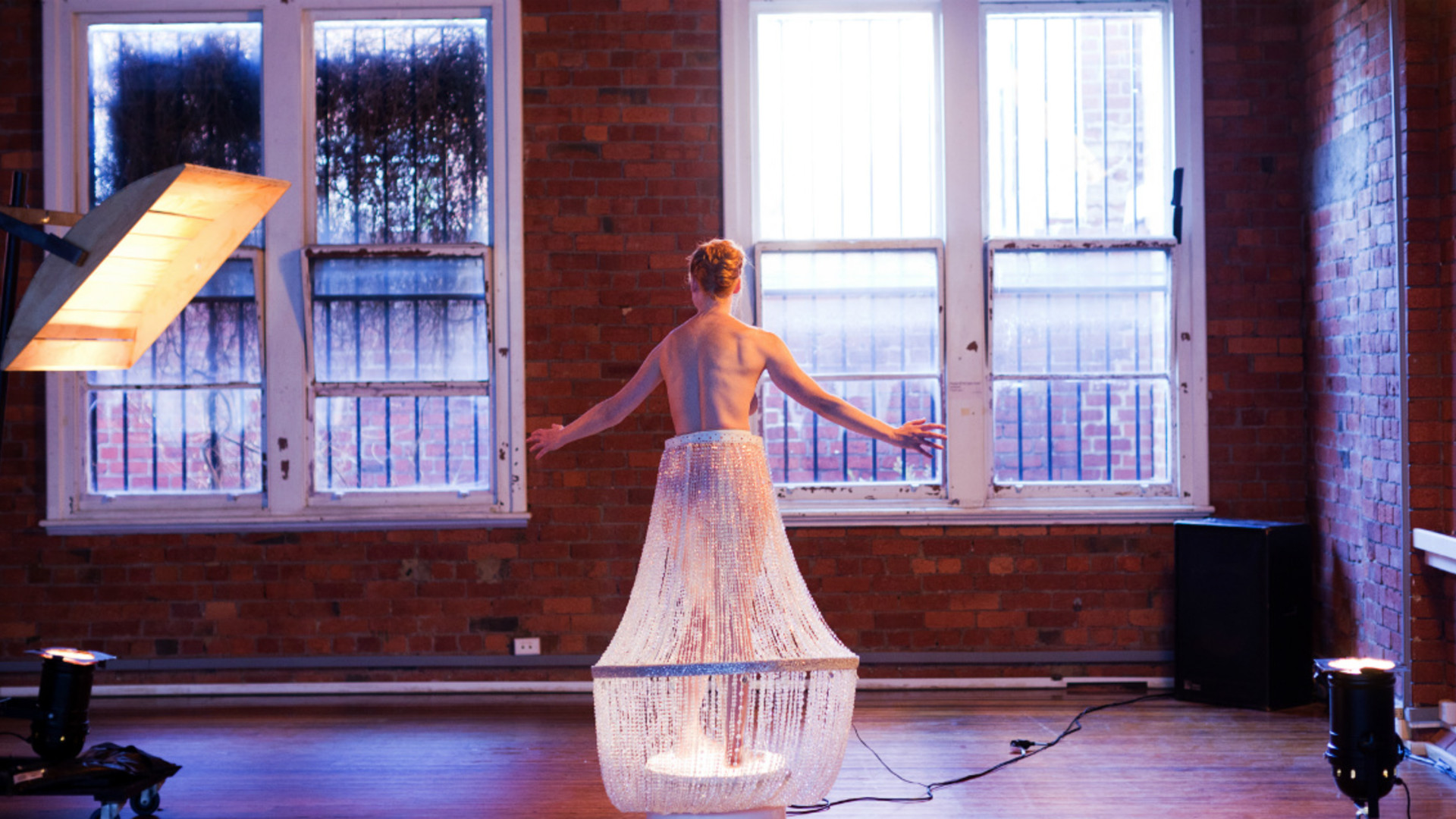 A topless woman seen from behind wearing a chandelier as a dress stands on a small white podium with a large square light to her left.