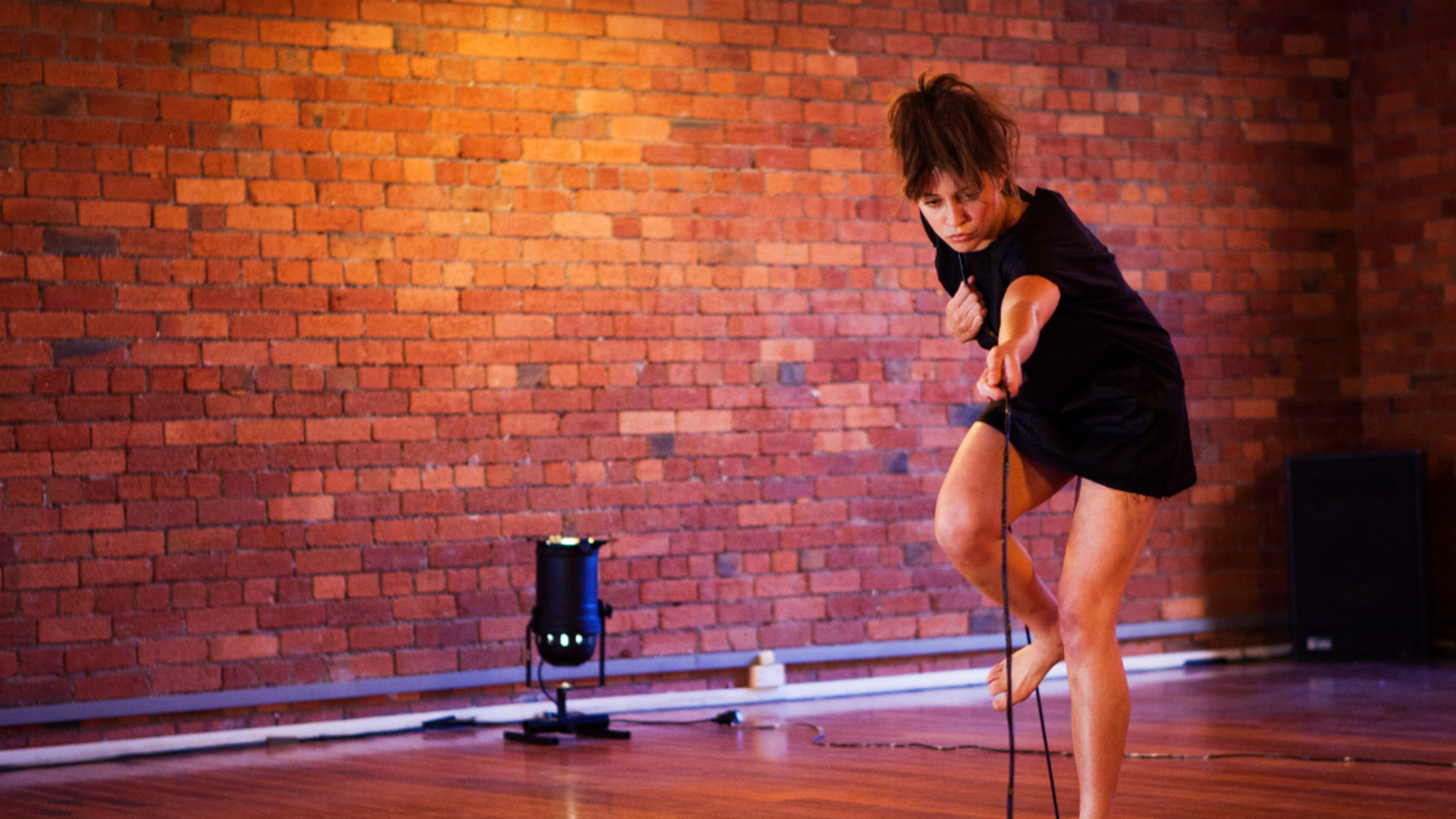 A woman in a short black dress pulls a wire that runs under the camera with a single light pointing up in the background in front of a brick wall