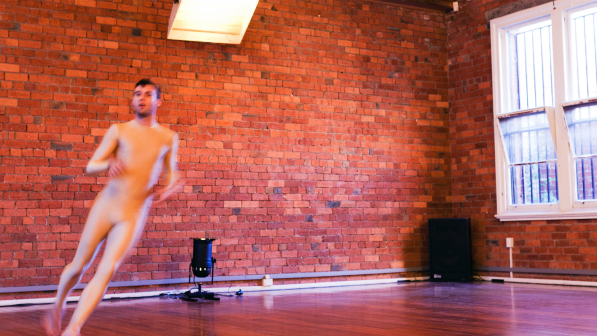 A young man, Rennie McDougall, in a flesh coloured unitard is blurred as he runs towards the camera in a room with a wooden floor and brick walls