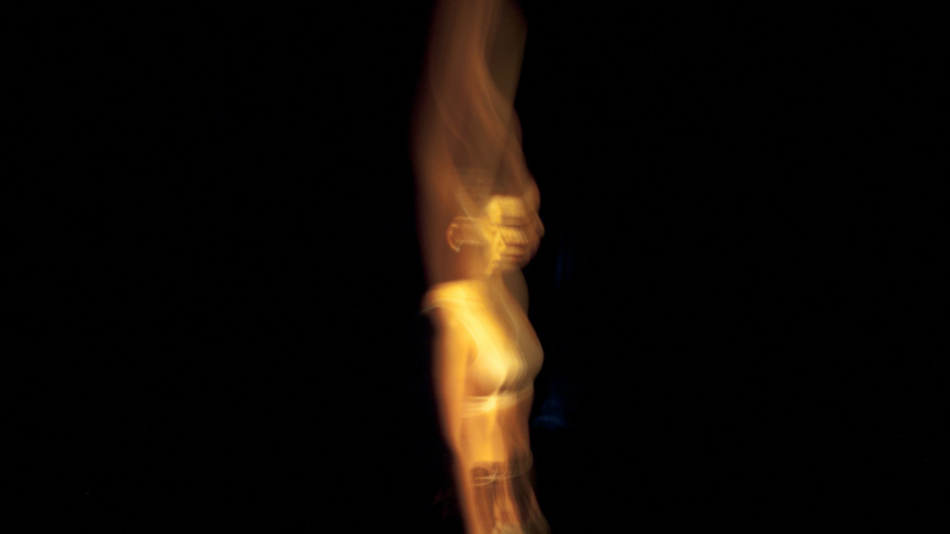 A spiralling, yellow blurred image of a woman in a black background