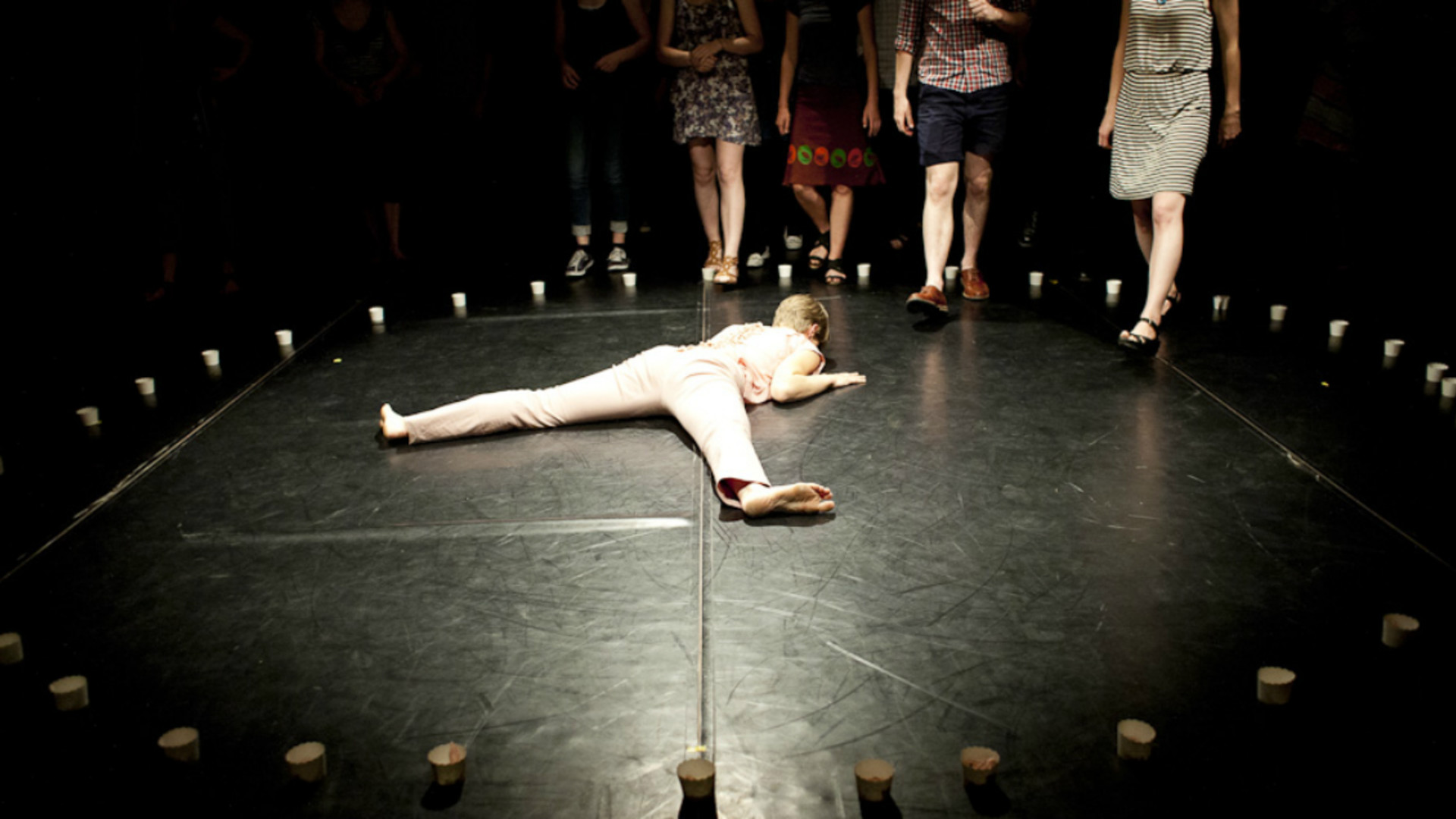 A dancer lies face down on a black floor in a spotlight surrounded by a ring of paper cups. The legs of four people are shown walking towards the dancer.