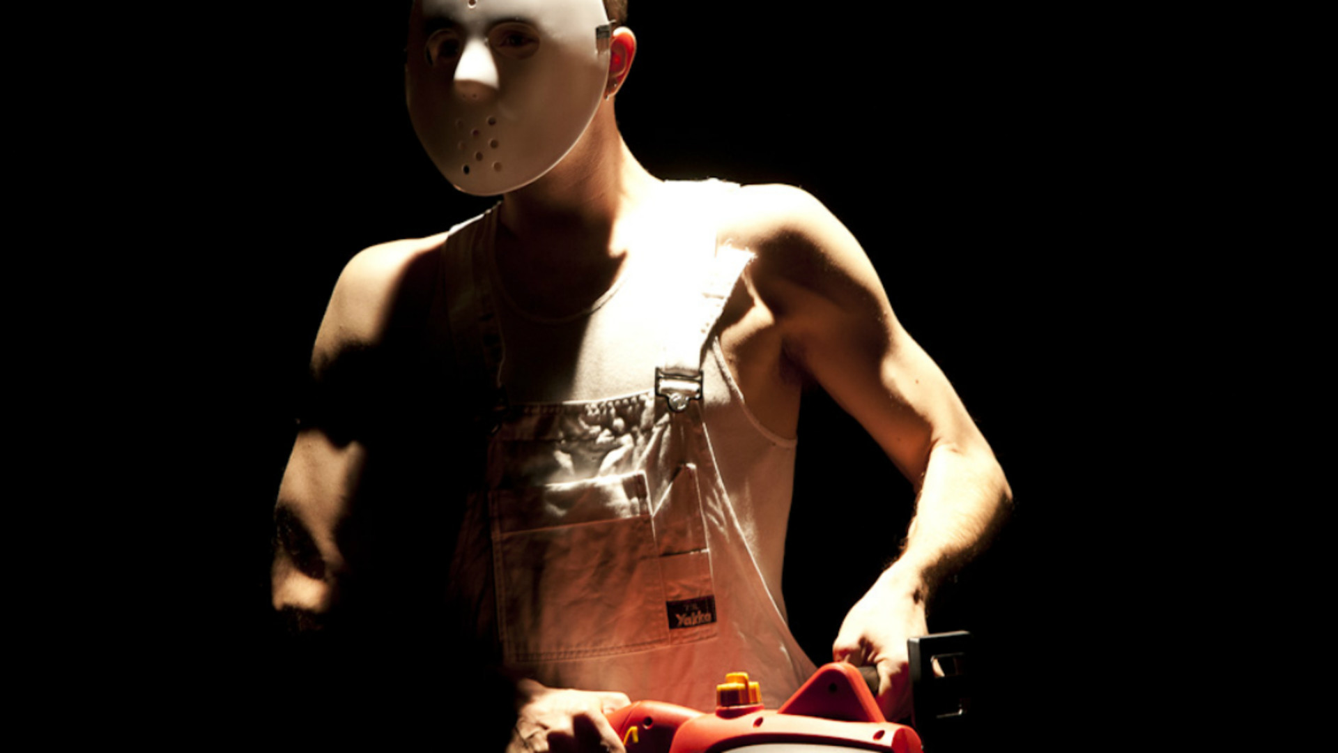 A close up of a man in white dungarees, singlet and white mask holding a red chainsaw is spotlit from above in a dark room
