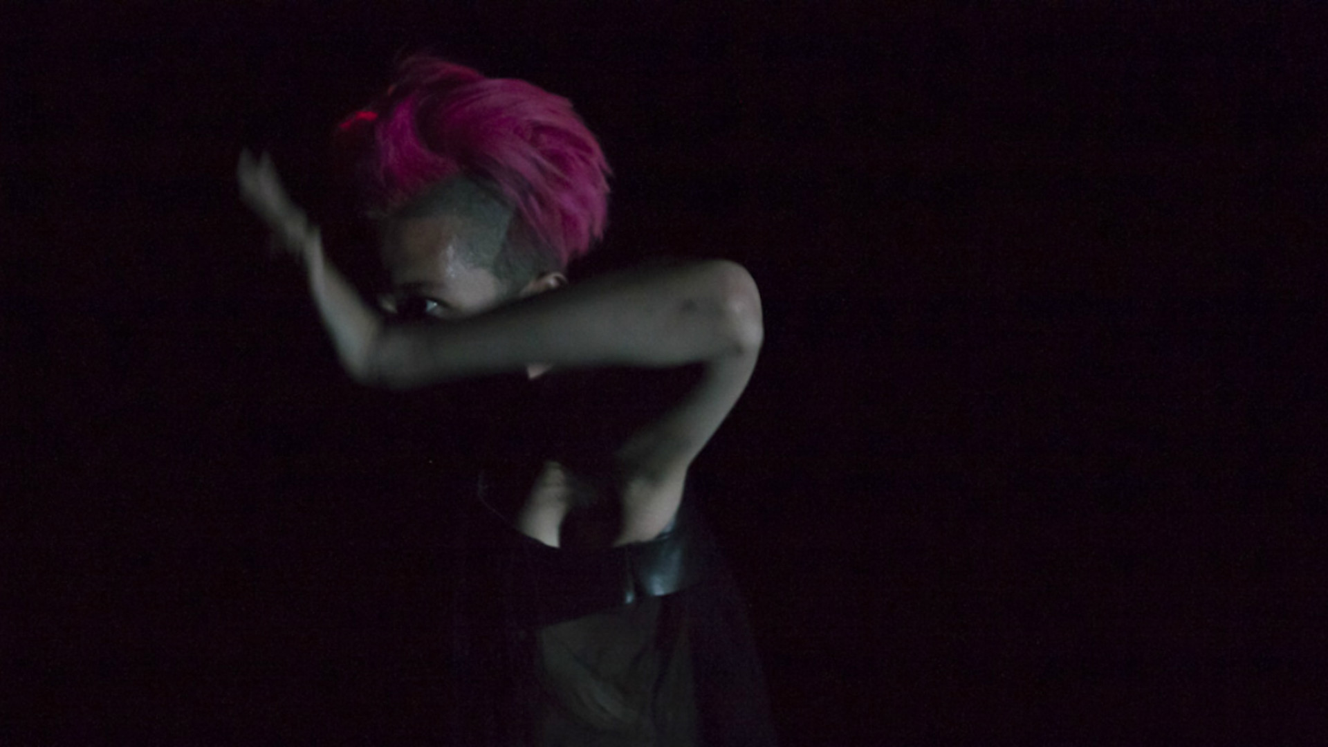 A close up of a dancer with bright pink hair whose right arm is moving in front of their face in a dark room.