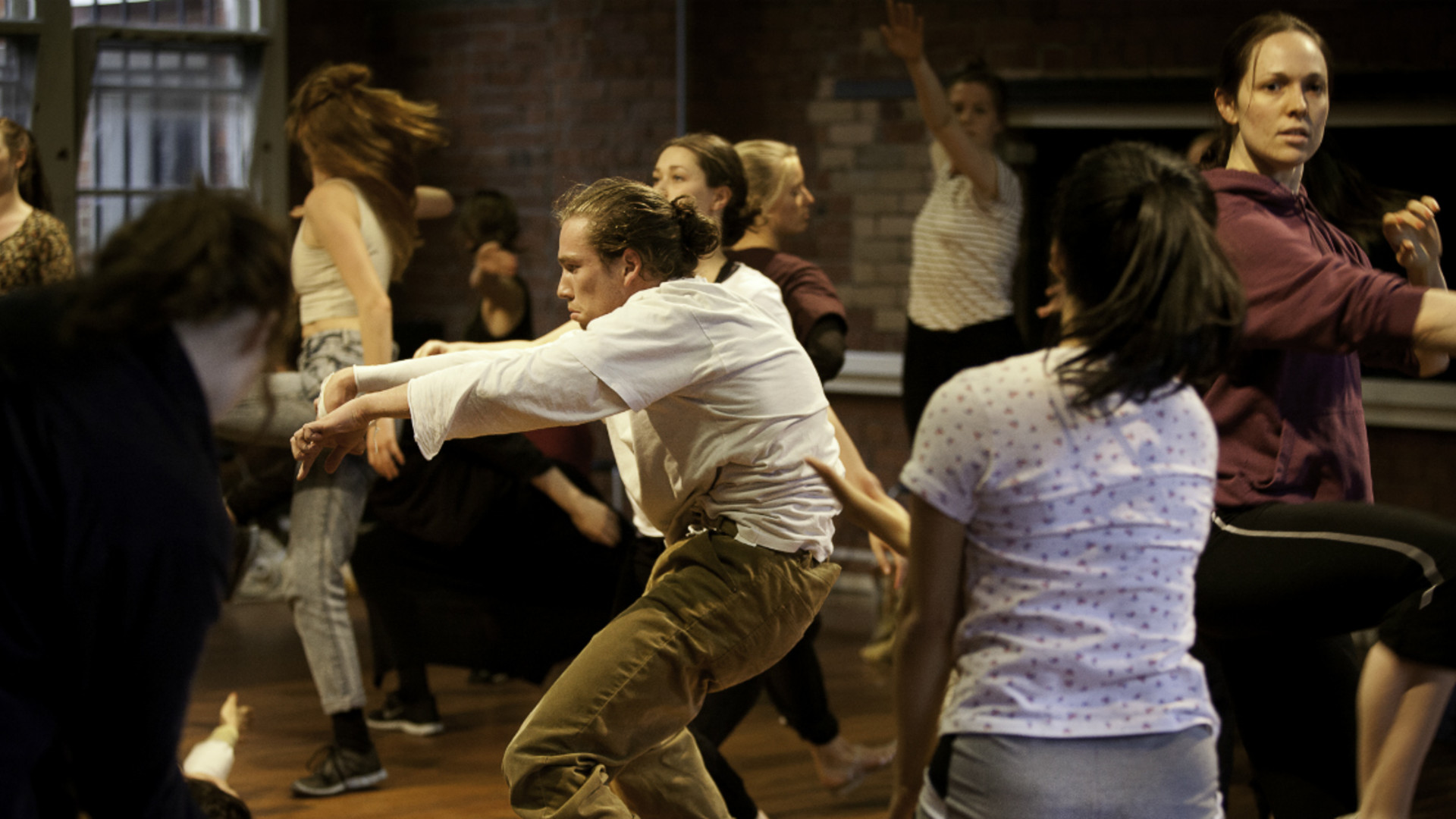 A large number of dancers dressed in everyday clothes energetically moving in a red brick room with a wooden floor.