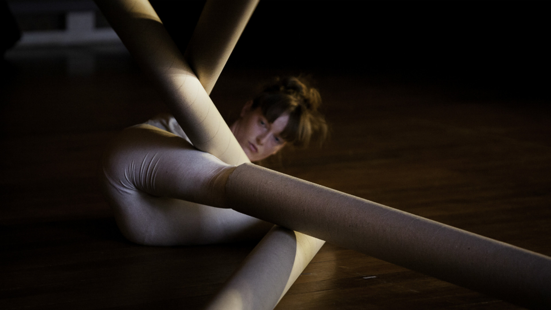 A dancer dressed in white lies on the ground with arms and legs in long cardboard tubes that are angled across one another