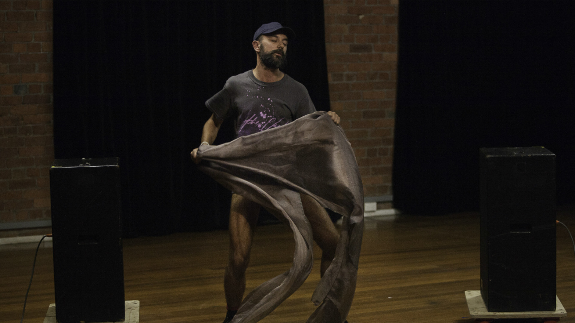 A man with a beard and black t-shirt dancers with eyes closed holding grey material between two black speaks on the wooden floor