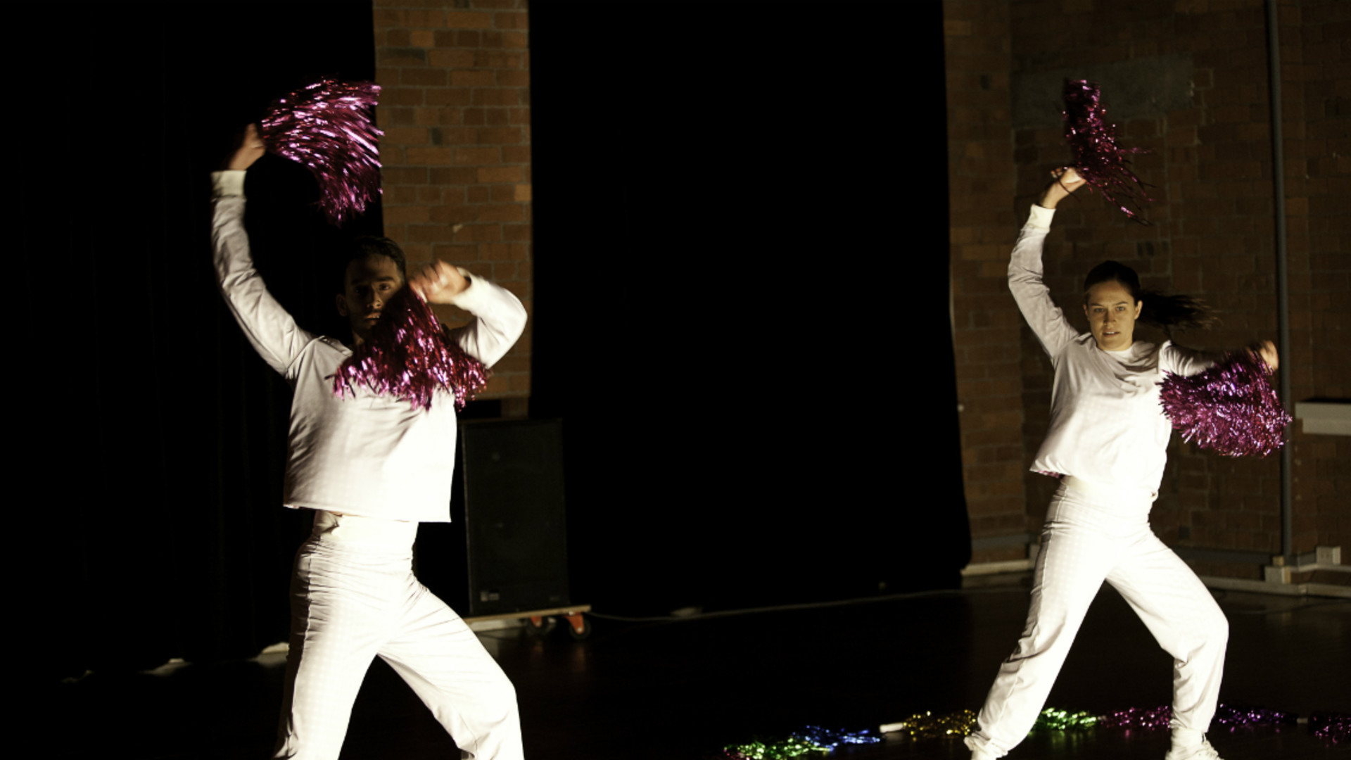 Two dancers dressed in white dance energetically and in unison with pink glittery pom poms