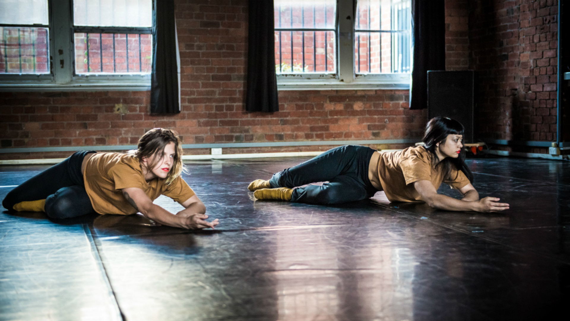 Two dancers lie across the floor, reaching out with one arm.