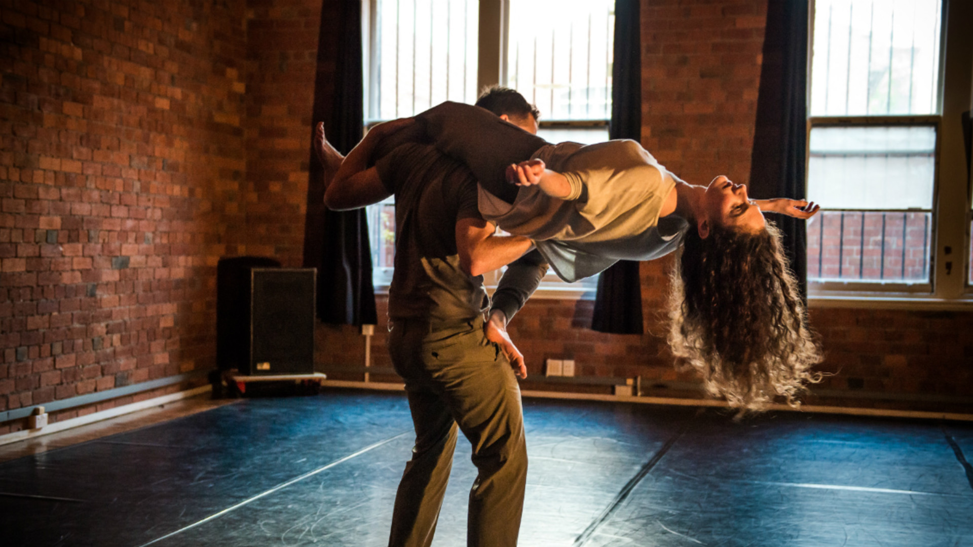 One dancer holds another dancer, with her leg arching over his back and her arms held out wide.