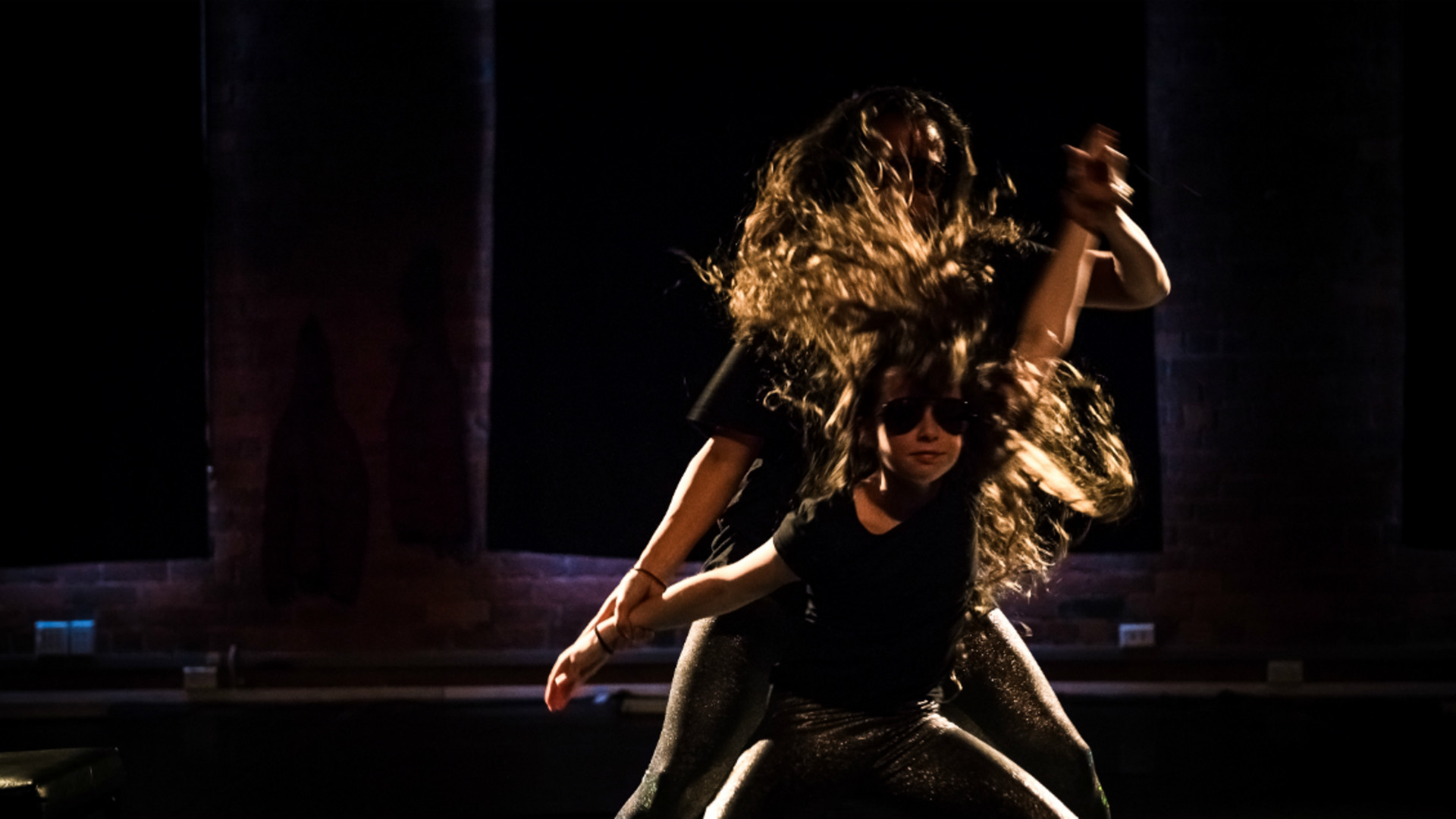One dancer stands in front of the other, their hands linked and hair flying outward.