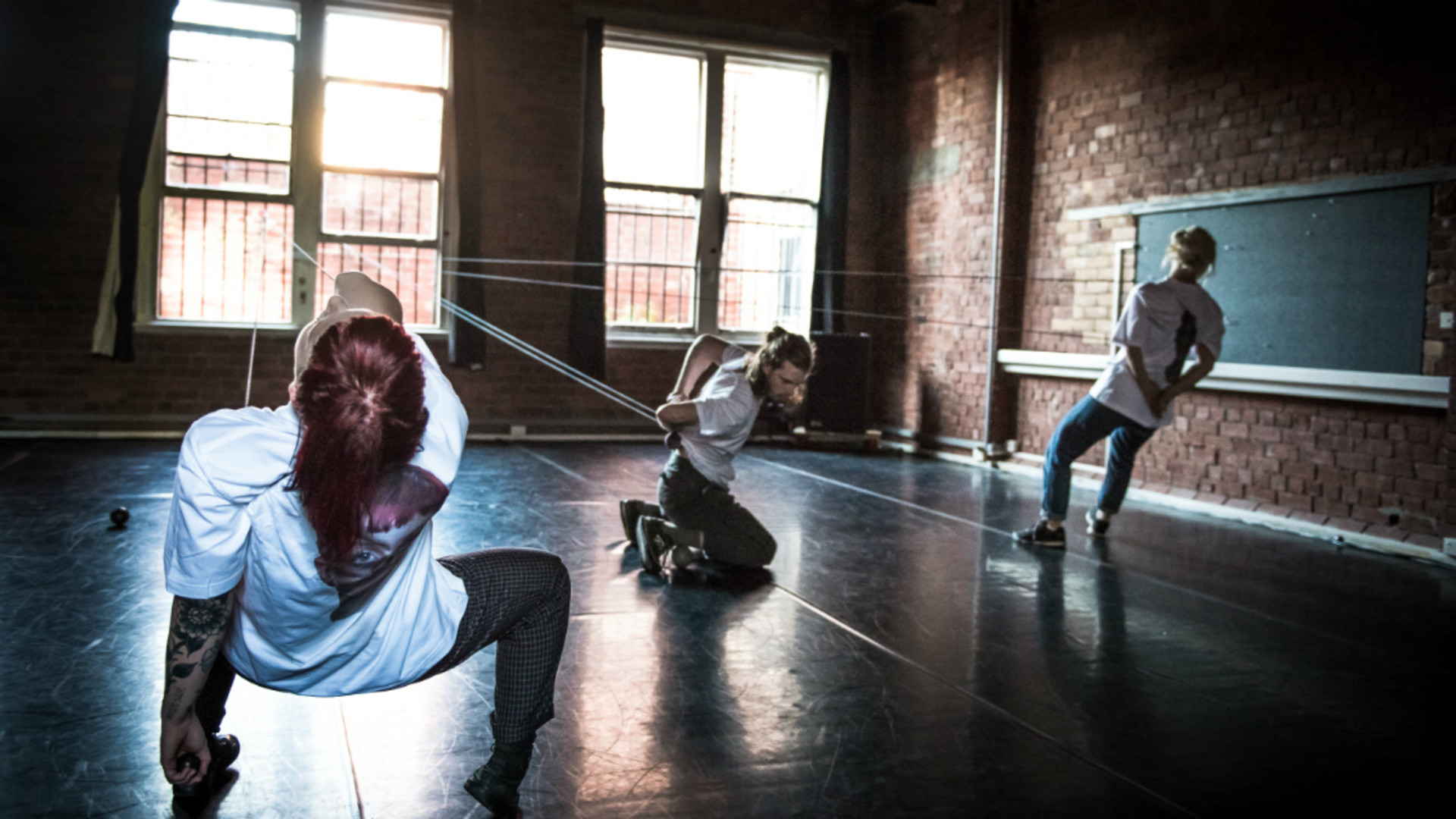Three dancers lean at different angels along taut white ropes.