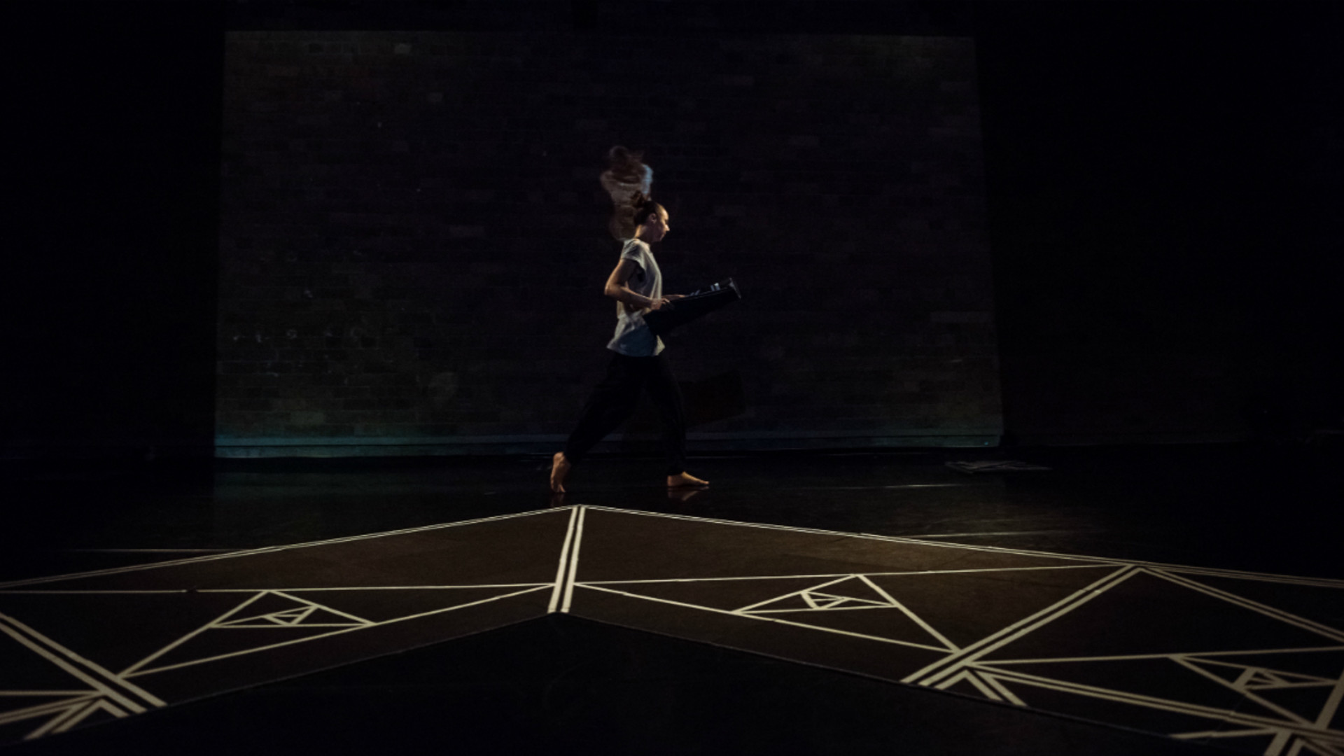 A dancer runs along a black floor with white geometric shapes painted on it.