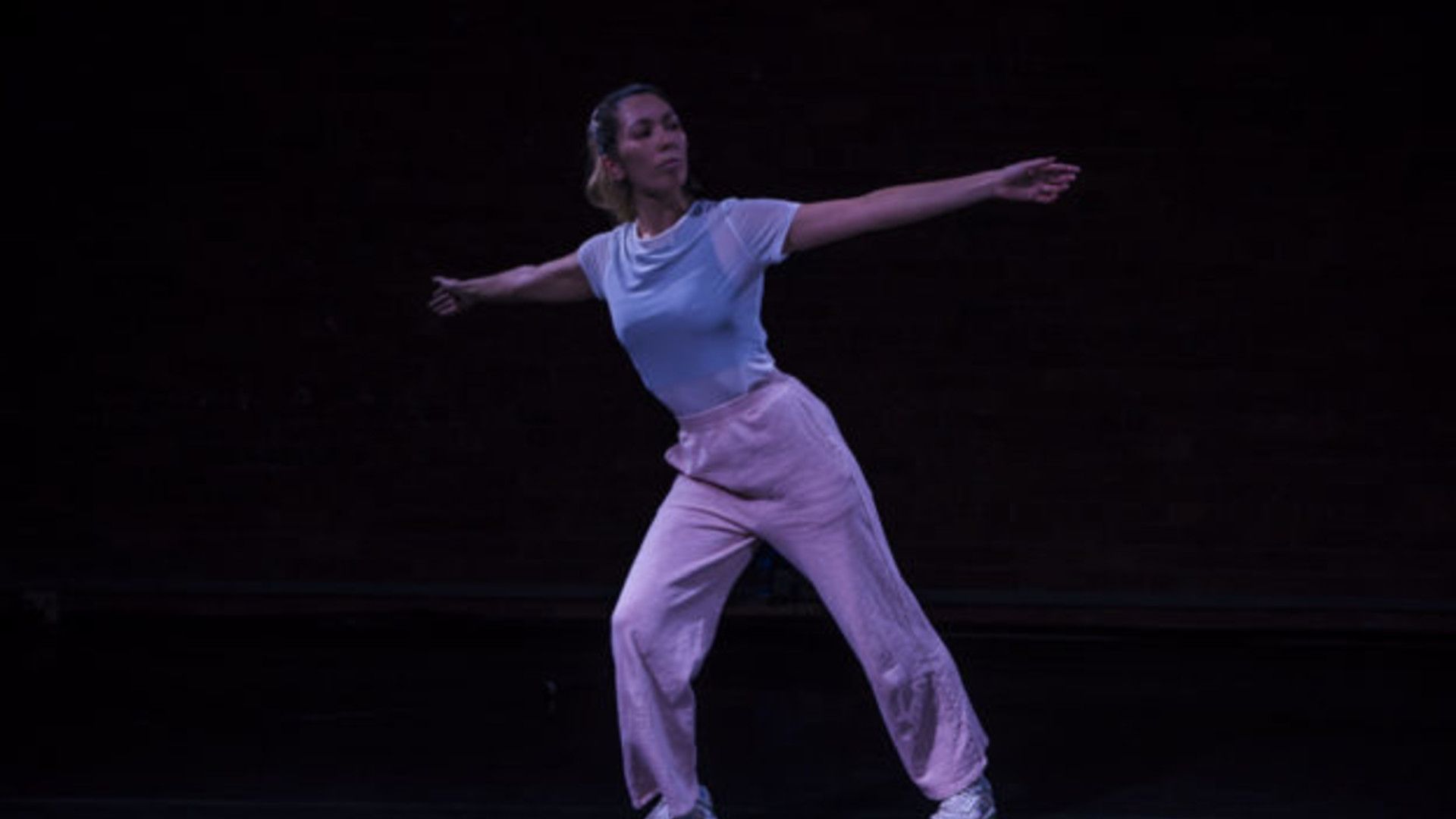 A dancer stands with one knee bend and both arms outstretched.