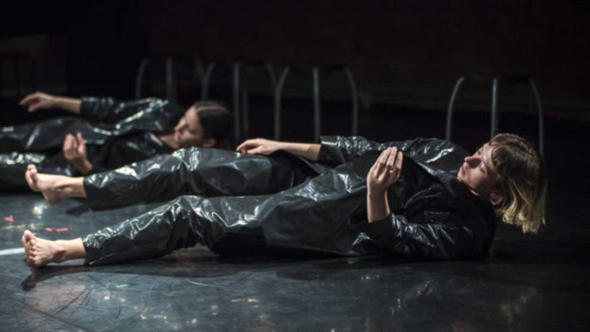 Two dancers lie on their backs, their necks craning upward.