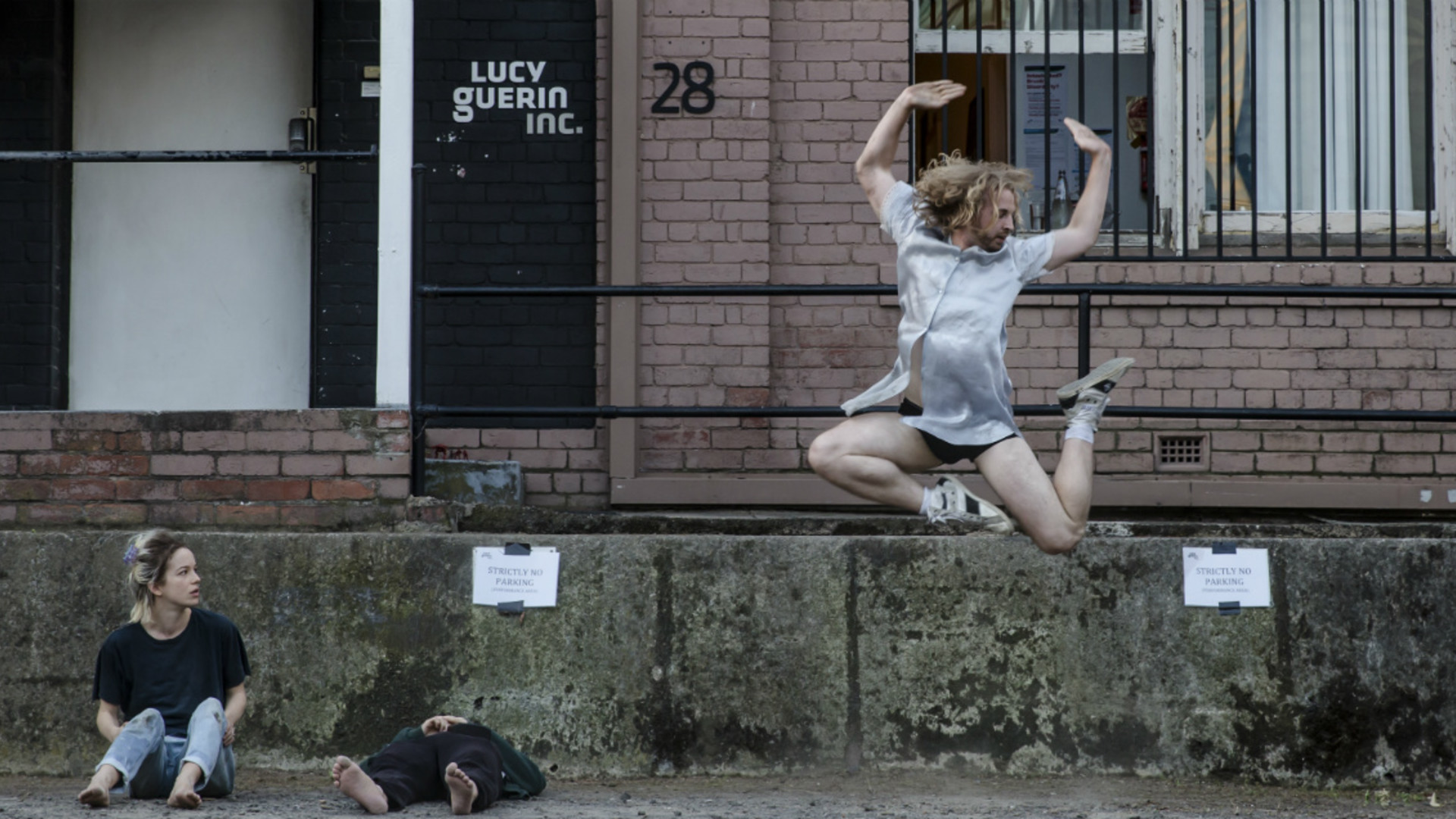 One performer leaps in the air while another is lying on the ground and another is seated.