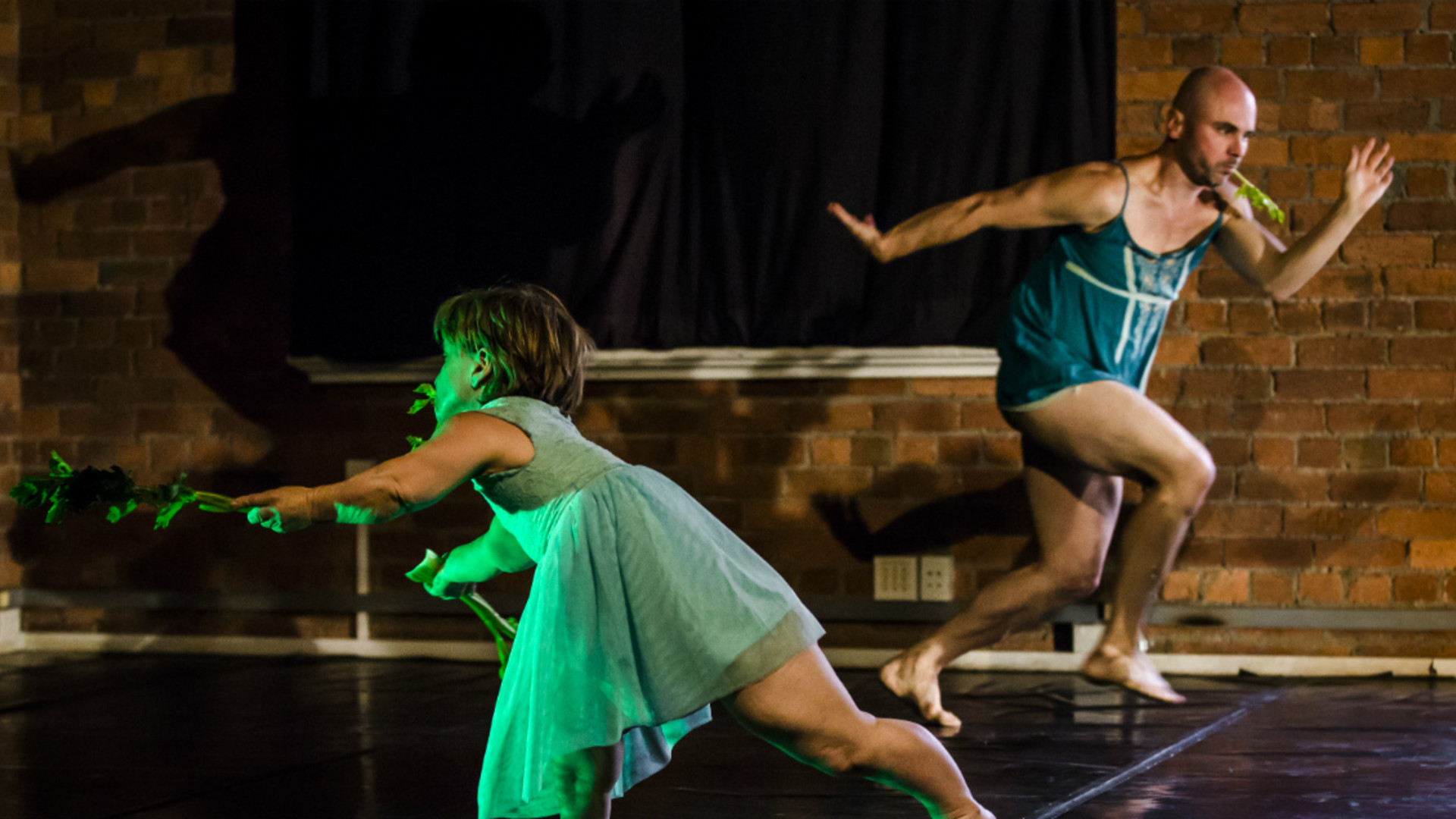 Two dancers run past each other in opposite directions, eating celery.
