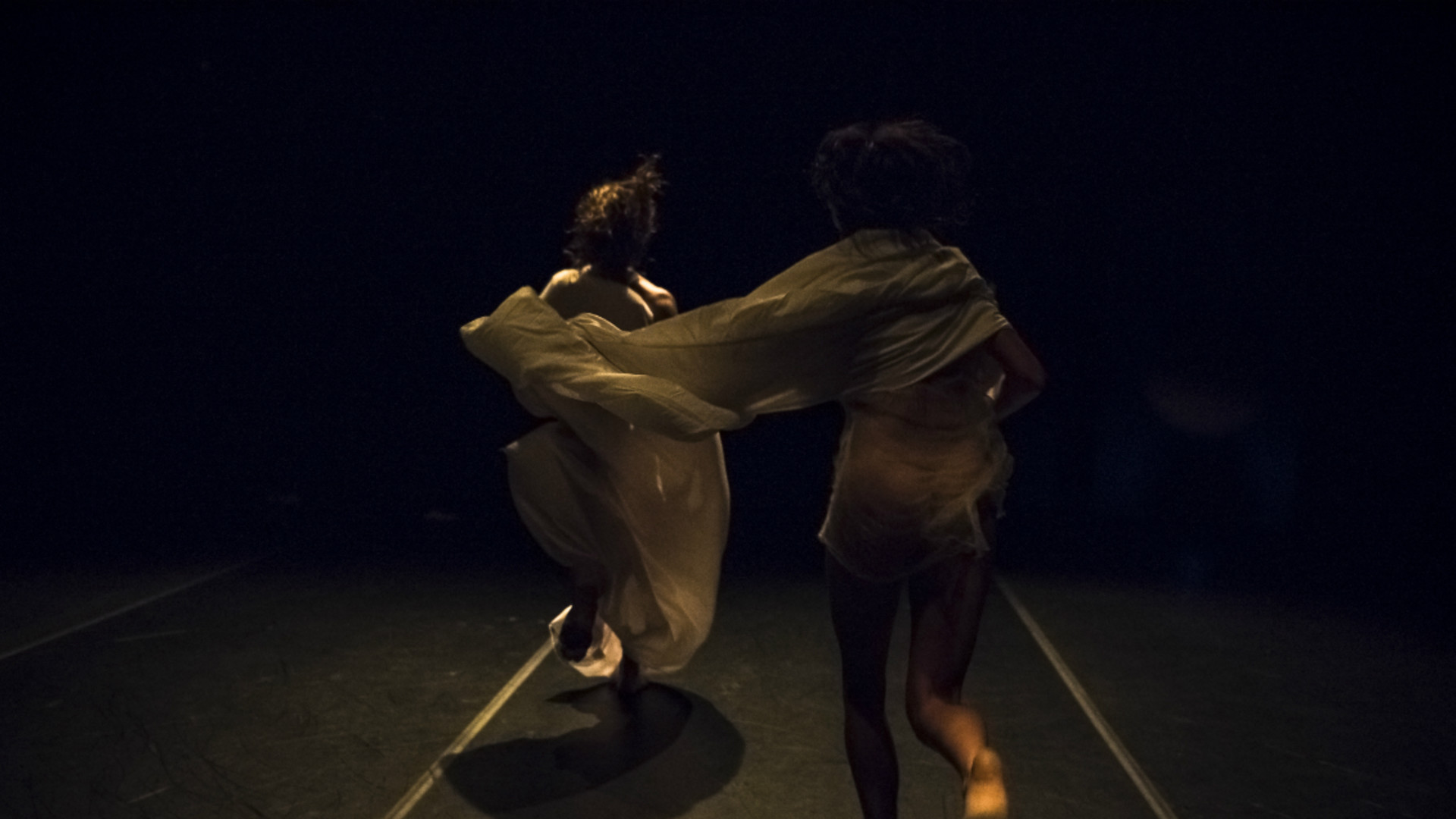 Two dancers run away from the camera dressed in white sheets in a semi-dark room
