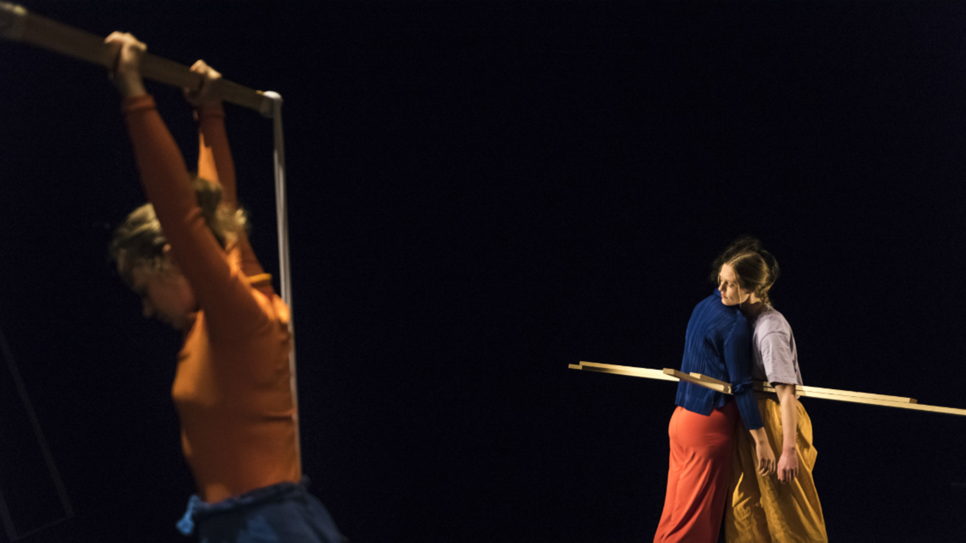 A dancer in the foreground stands and holds up a wooden frame, while two dancers embrace int he background with long wooden poles suspended at their waists