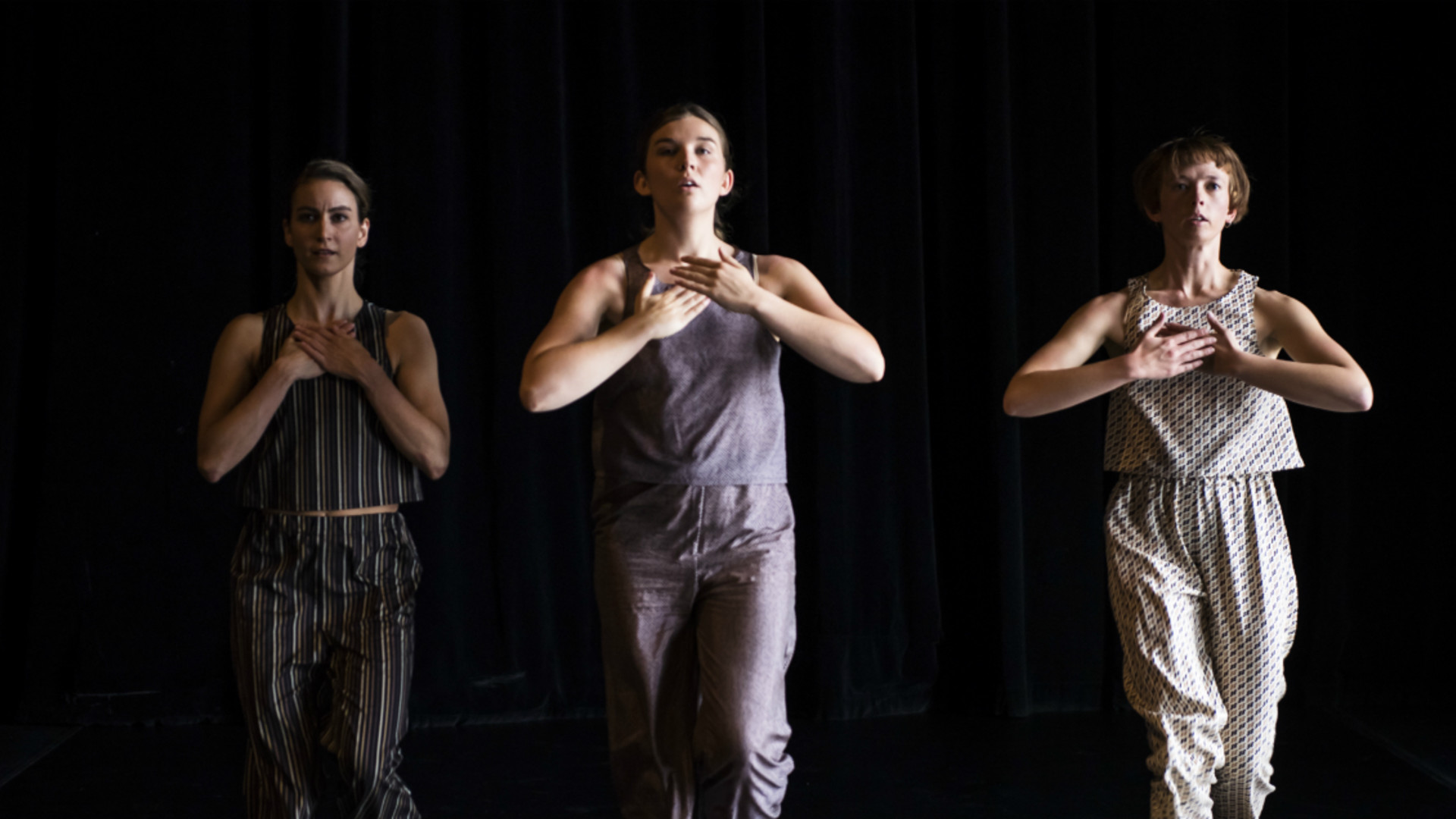 Three dancers walk forwards looking over the camera and hold their hands to their chest in unison